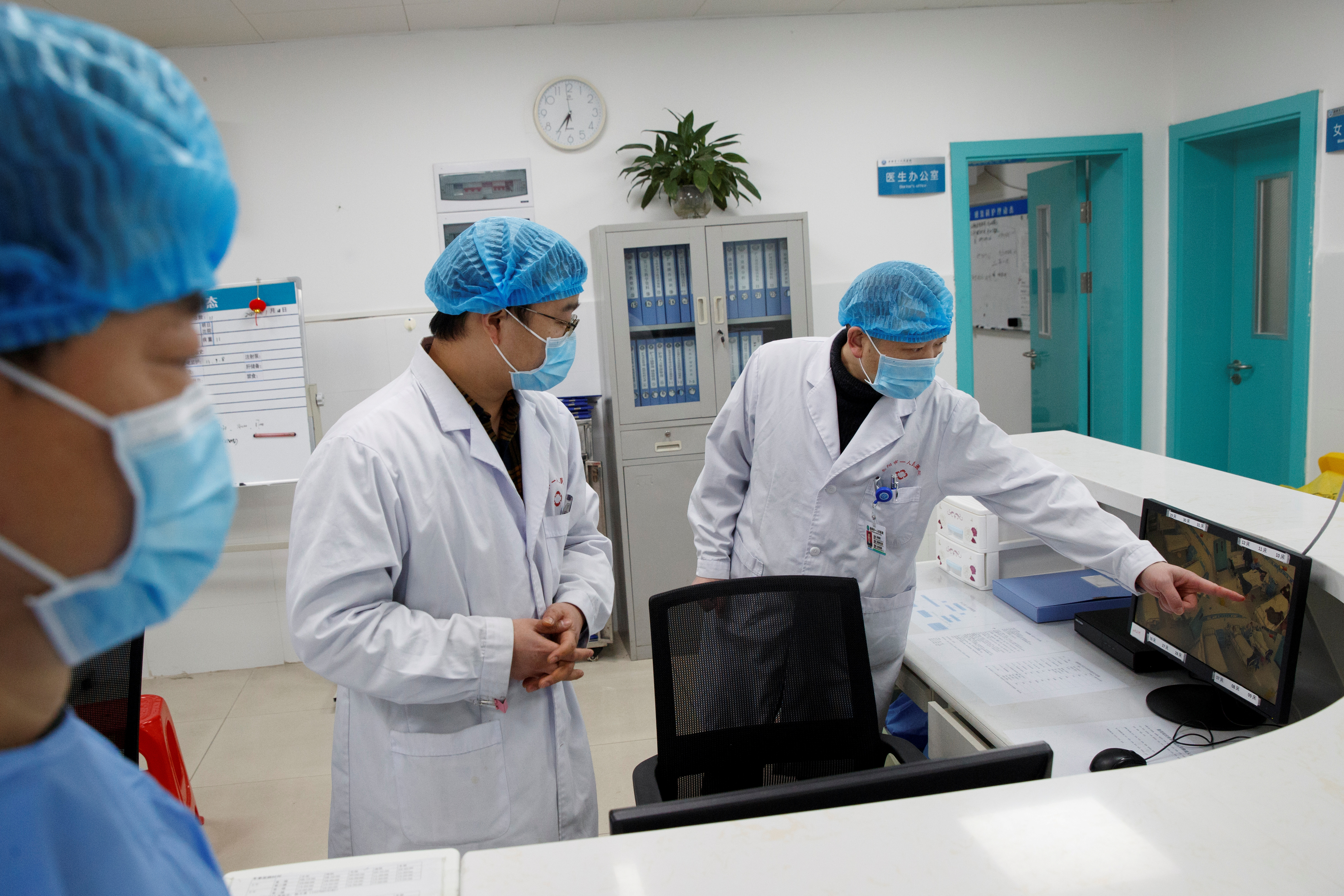 FILE PHOTO: Doctors look at a screen that shows the ward where patients who are infected with the coronavirus are treated at the First People's Hospital in Yueyang, Hunan Province, near the border to Hubei Province, which is under partial lockdown after an outbreak of a new coronavirus, in China January 28, 2020.  REUTERS/Thomas Peter/File Photo