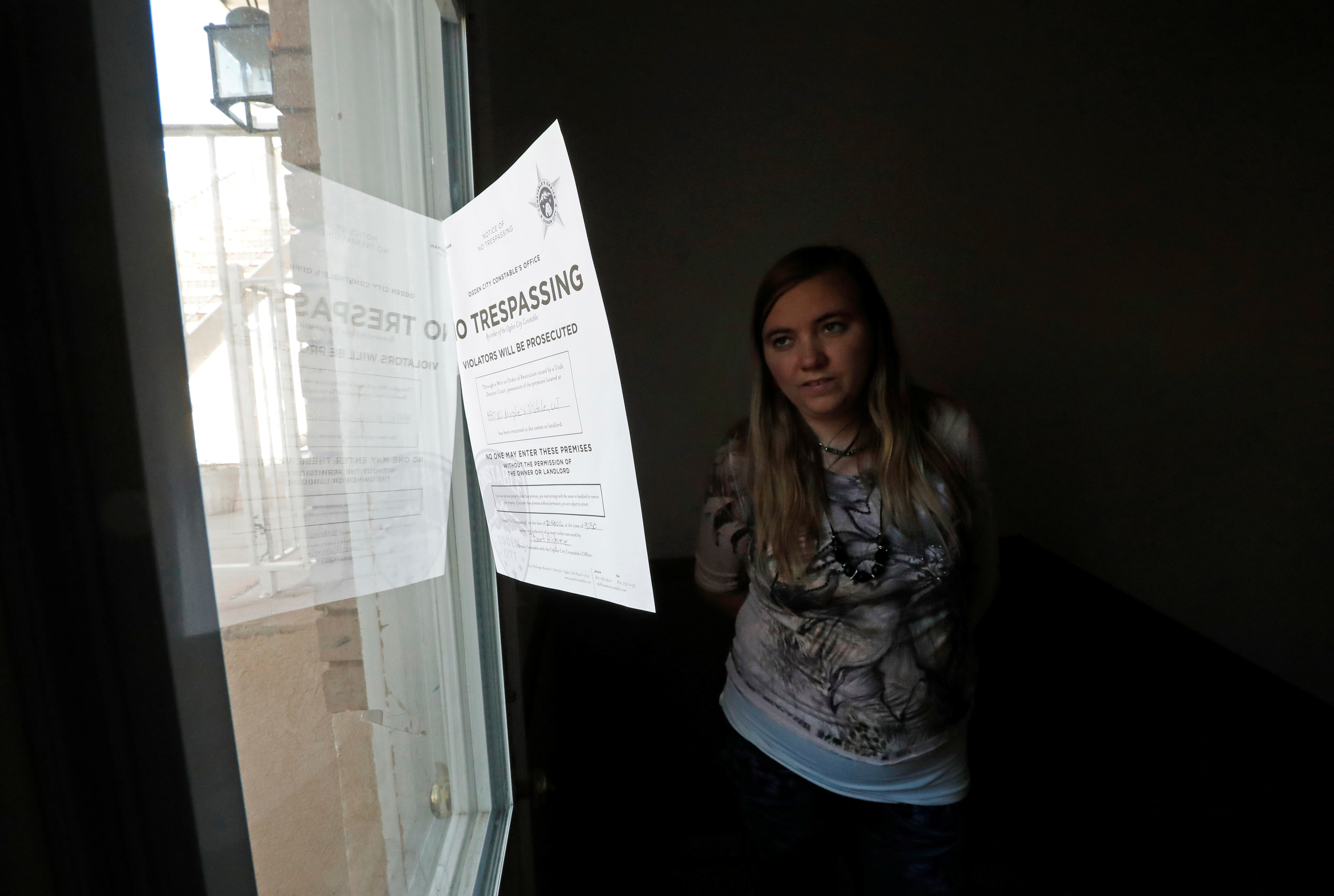 Briell Decker, the 65th wife of jailed Fundamentalist Church of Jesus Christ of Latter-Day Saints (FLDS Church) polygamist prophet leader Warren Jeffs, looks at an eviction notice on the window at his compound, where he lived for several years, in Hildale, Utah, U.S., May 3, 2017. She is in the process of purchasing the compound. Picture taken May 3, 2017.  REUTERS/George Frey