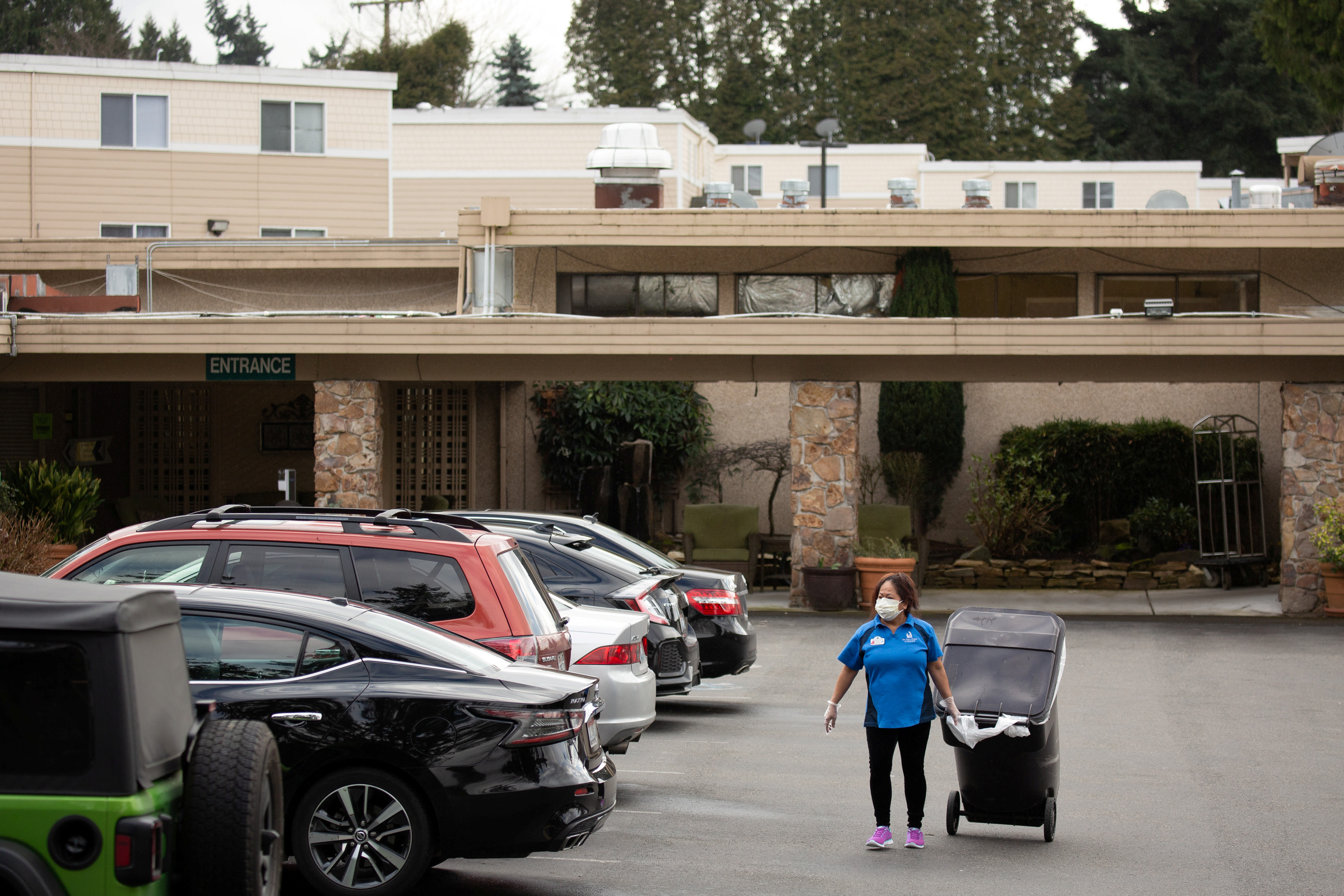 A worker carries a garbage can while wearing a mask at the Life Care Center of Kirkland, where two of three confirmed coronavirus cases in the state had links to the long-term care facility in Kirkland, Washington, U.S. March 1, 2020. REUTERS/David Ryder