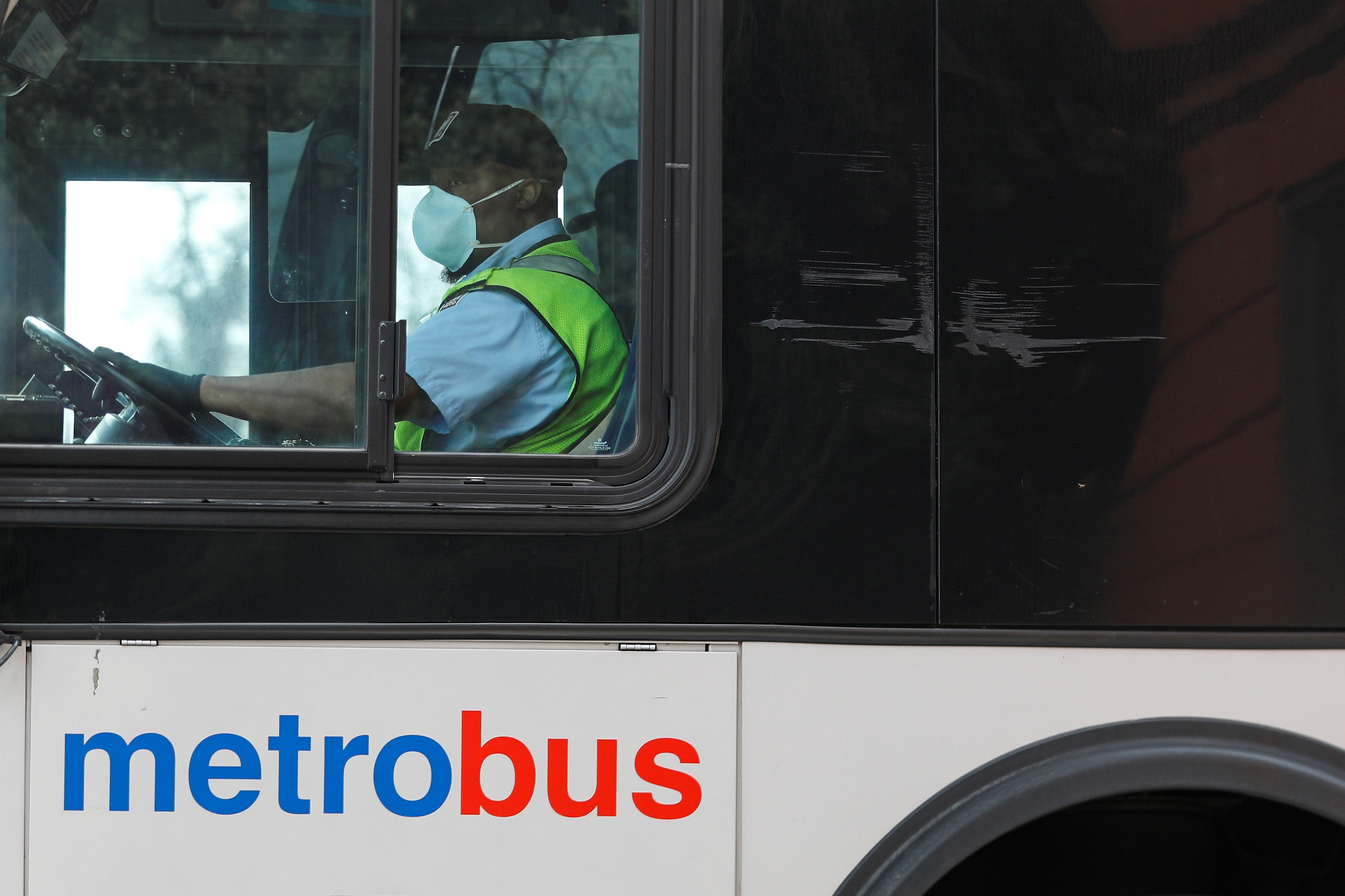 A Washington Metro bus driver passes along a route wearing a face mask, as Mayor Muriel Bowser issued a State of Emergency in response to the coronavirus disease (COVID-19) in Washington, U.S., March 20, 2020. REUTERS/Tom Brenner