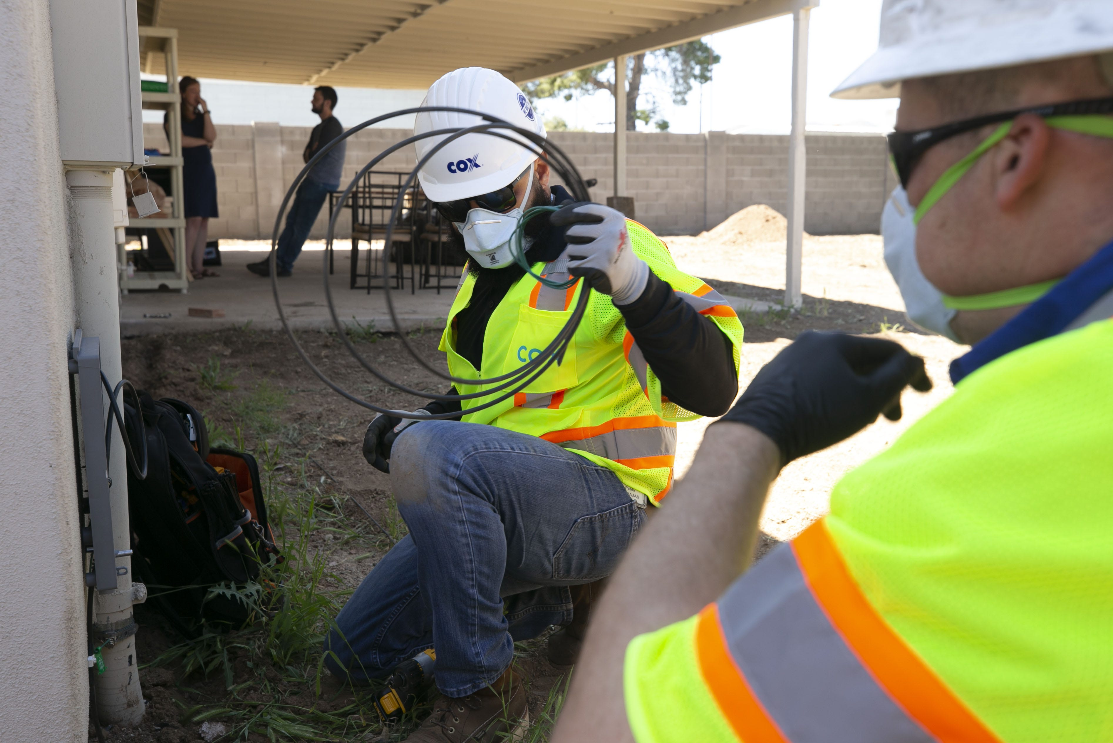 Pablo Barajas (center) and Brandon Petersen, both with Cox Communications, install internet at the Phoenix home of Tyler and Alex Palmer (background) on April 15, 2020. Cox Communications installers have changed how they do their jobs and avoid entering customers' homes in almost all situations because of the new coronavirus pandemic. The Palmers moved into their home in mid-March and have been without internet since.Cable Internet Service Coronavirus Covid 19