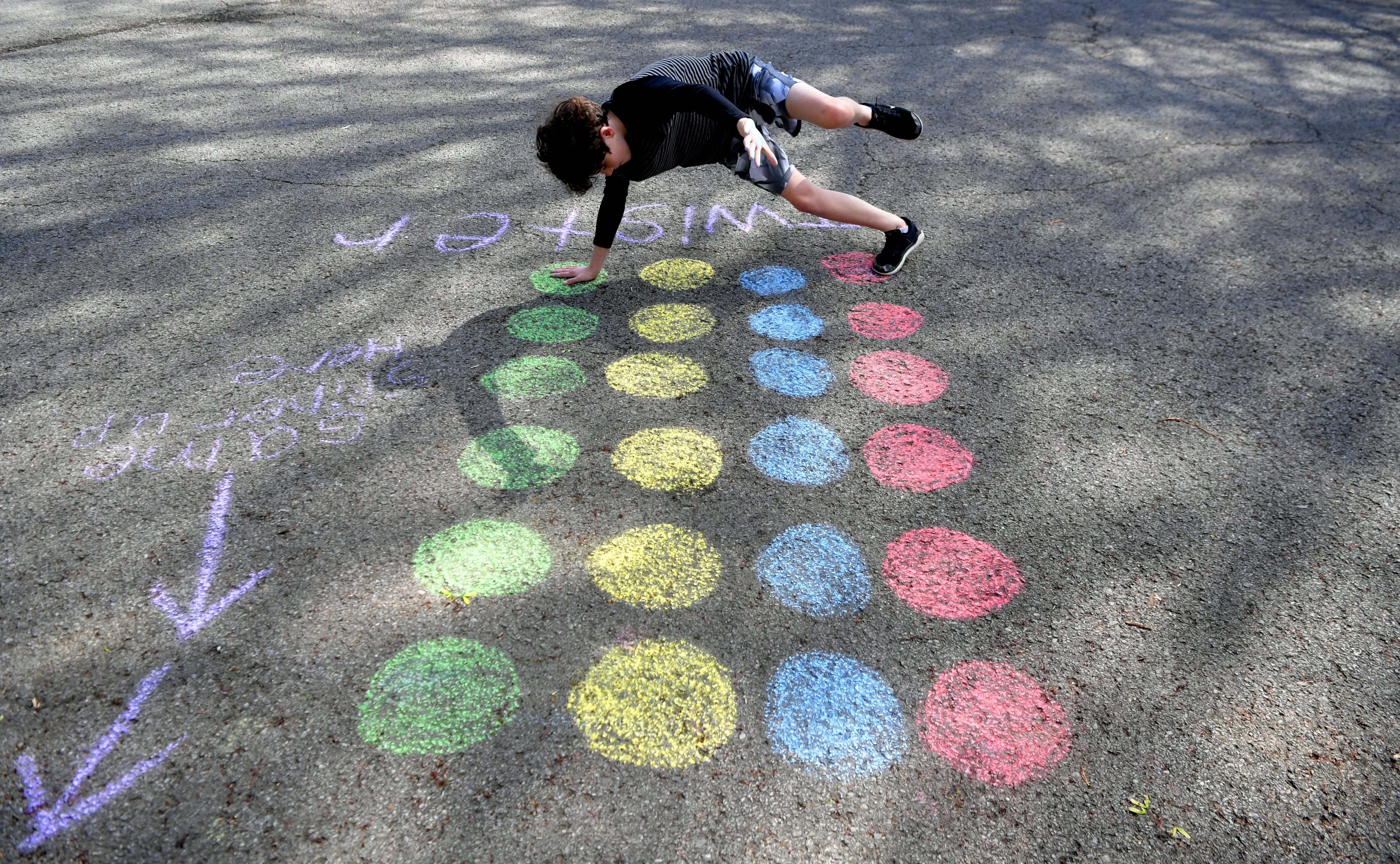 """Franklin's Forrest Crossing neighborhood has created a  """"Social Distancing Calendar of Fun.""""   On Wednesday, some residents like Eli Ecken,11, plays Twister during neighborhood's chalk walk Franklin on  April 1, 2020.Sem 1233"""
