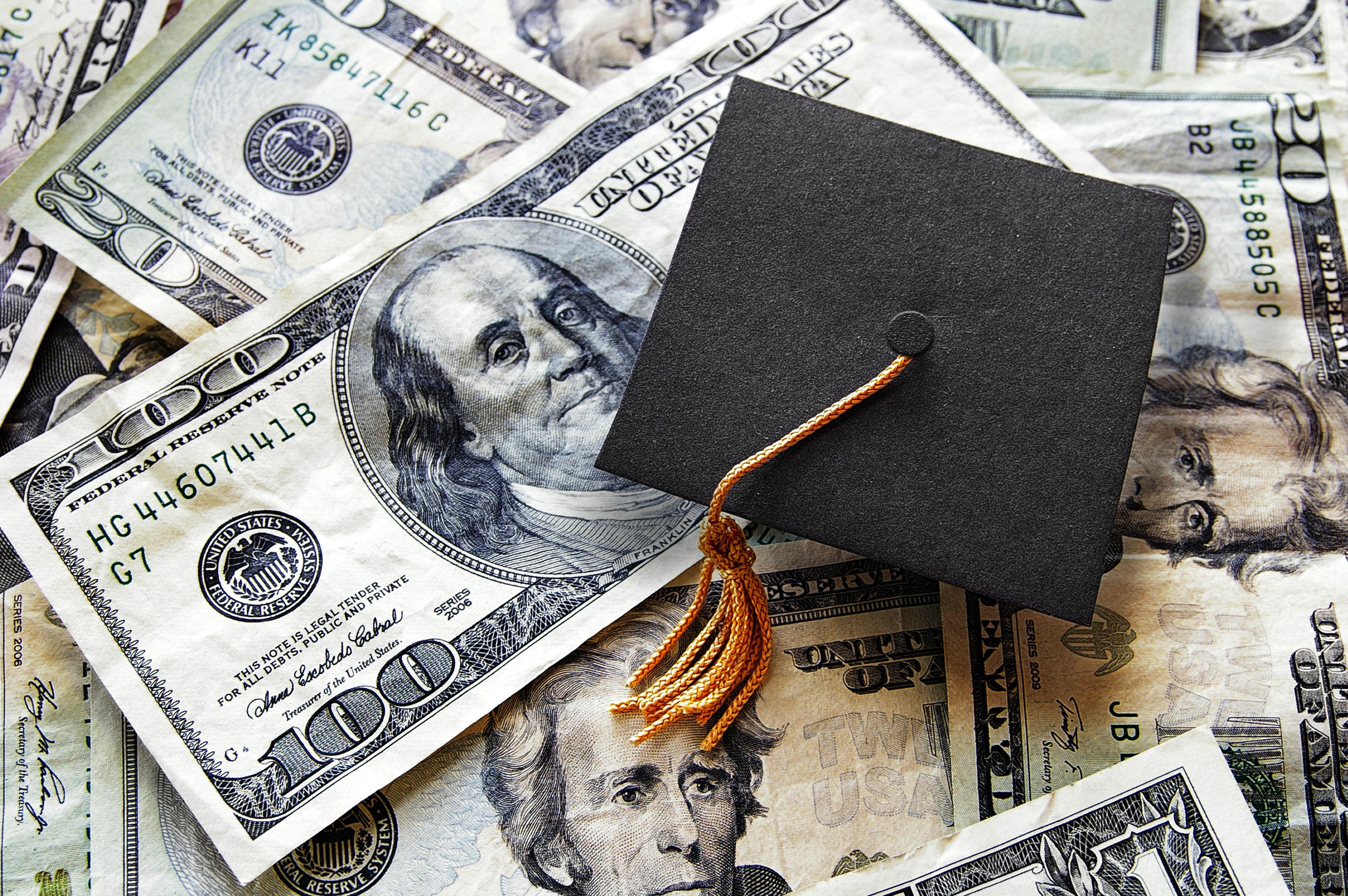 Miniature graduation cap on hundred dollar bills