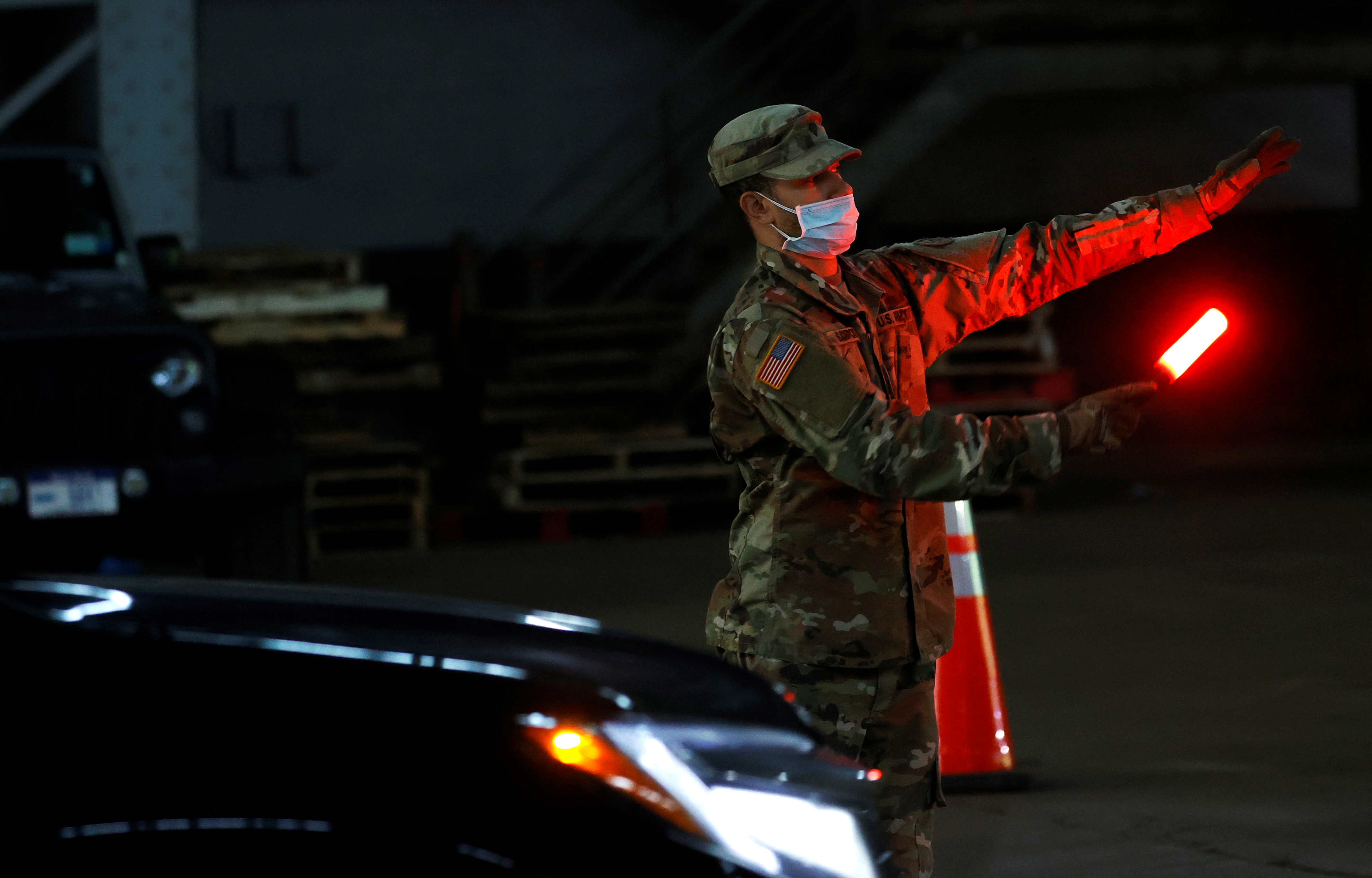 A U.S. Army National Guard soldier wears a protective face mask while directing vehicles to pick up food for delivery to residents in need, at the Kingsbridge Armory which is being used as a temporary food distribution center during the outbreak of the coronavirus disease (COVID-19) in the Bronx borough of New York City, New York, U.S., April 21, 2020. REUTERS/Mike Segar