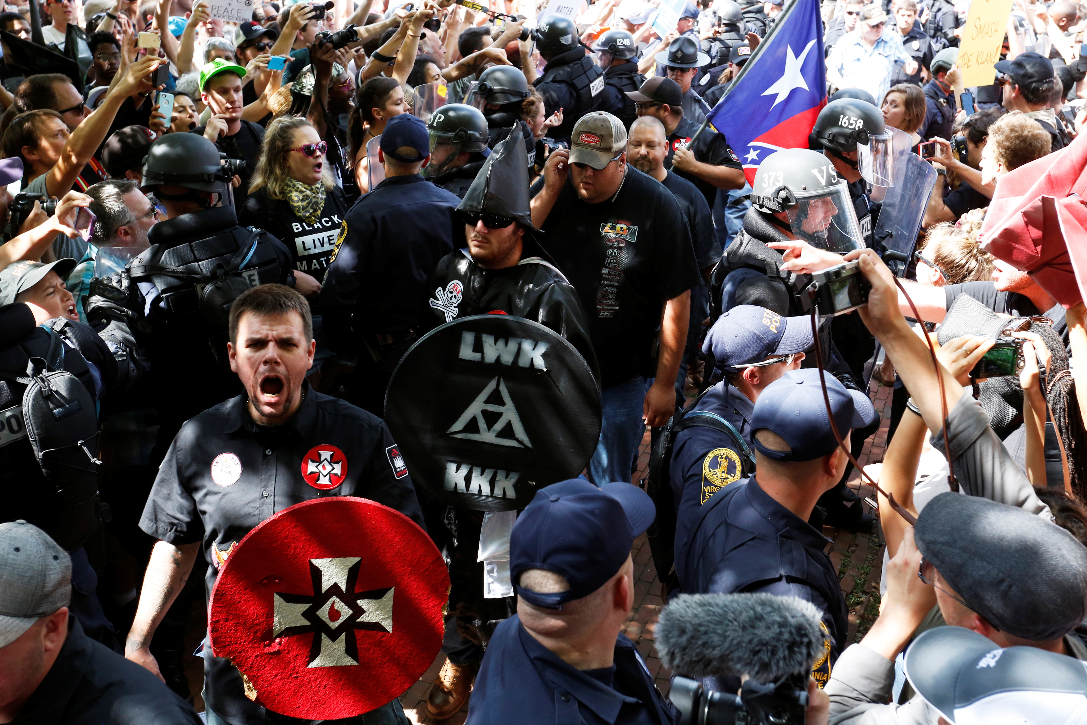 Riot police protect members of the Ku Klux Klan from counter-protesters as they arrive to rally in opposition to city proposals to remove or make changes to Confederate monuments in Charlottesville, Virginia, U.S. July 8, 2017. REUTERS/Jonathan Ernst
