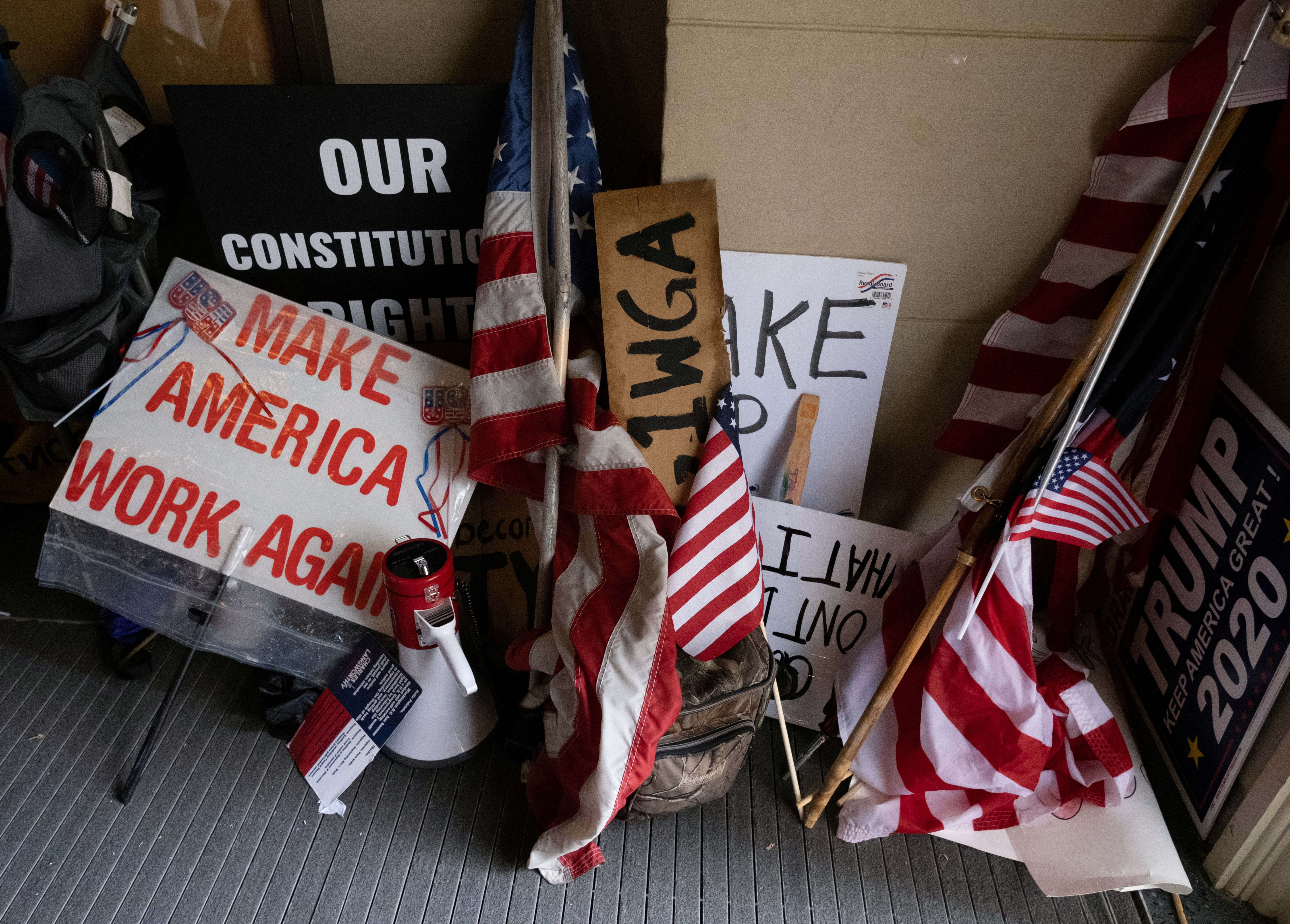 Protesters leave their flags and signs at the entrance of the state capitol building after protesters occupied the building during a vote to approve the extension of Governor Gretchen Whitmer's emergency declaration/stay-at-home order due to the coronavirus disease (COVID-19) outbreak, at the state capitol in Lansing, Michigan, U.S. April 30, 2020.  REUTERS/Seth Herald