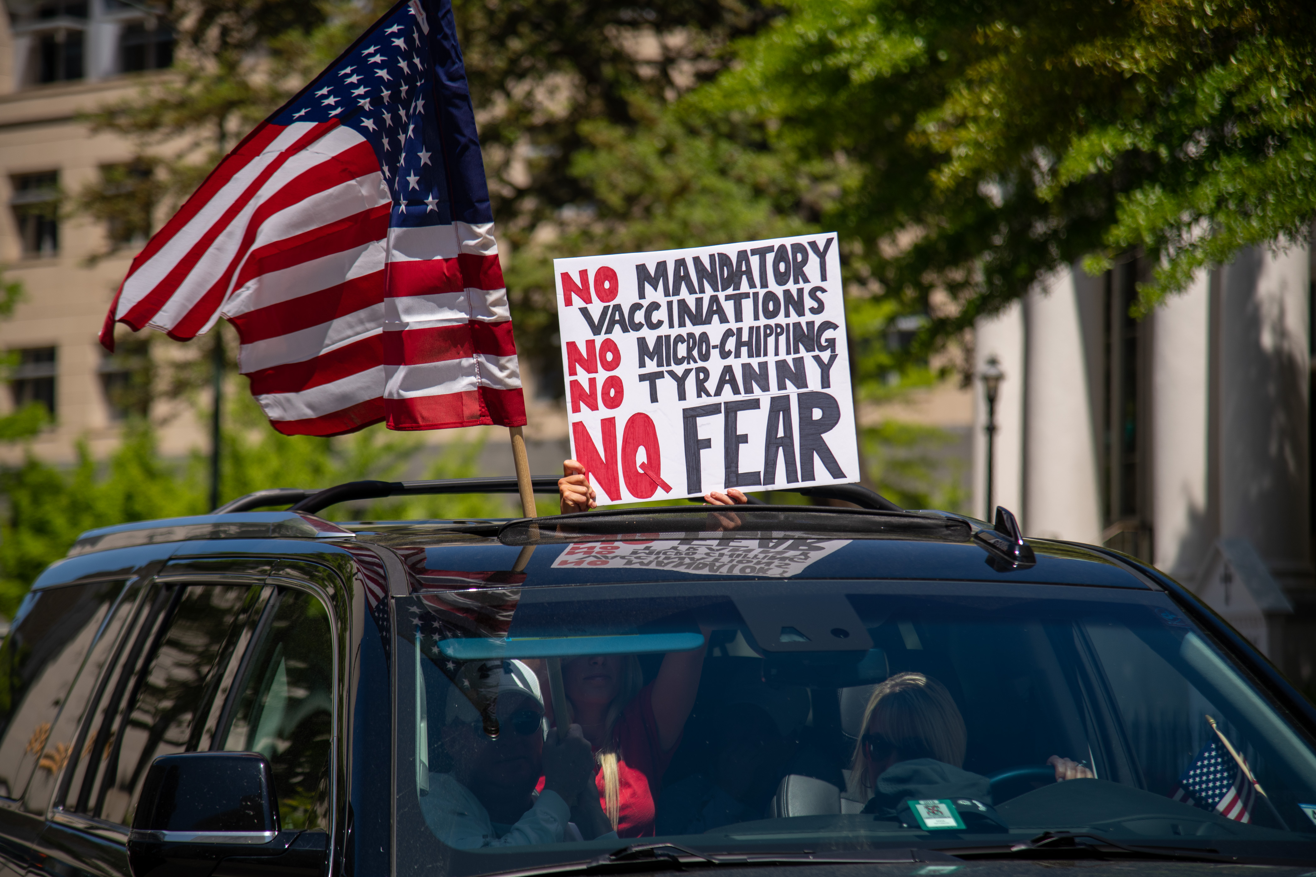 """A woman holds a sign voicing various conspiracy theories believed by QAnon followers out of the sunroof of a car at the """"Reopen Virginia"""" protest in Richmond on April 22nd, 2020.  Three Percenters are a movement that advocates for constitutional rights, and takes its name from the belief that only three percent of America took up arms against the British during the Revolutionary War. (Photo by Matthew Rodier/Sipa USA)No Use UK. No Use Germany."""