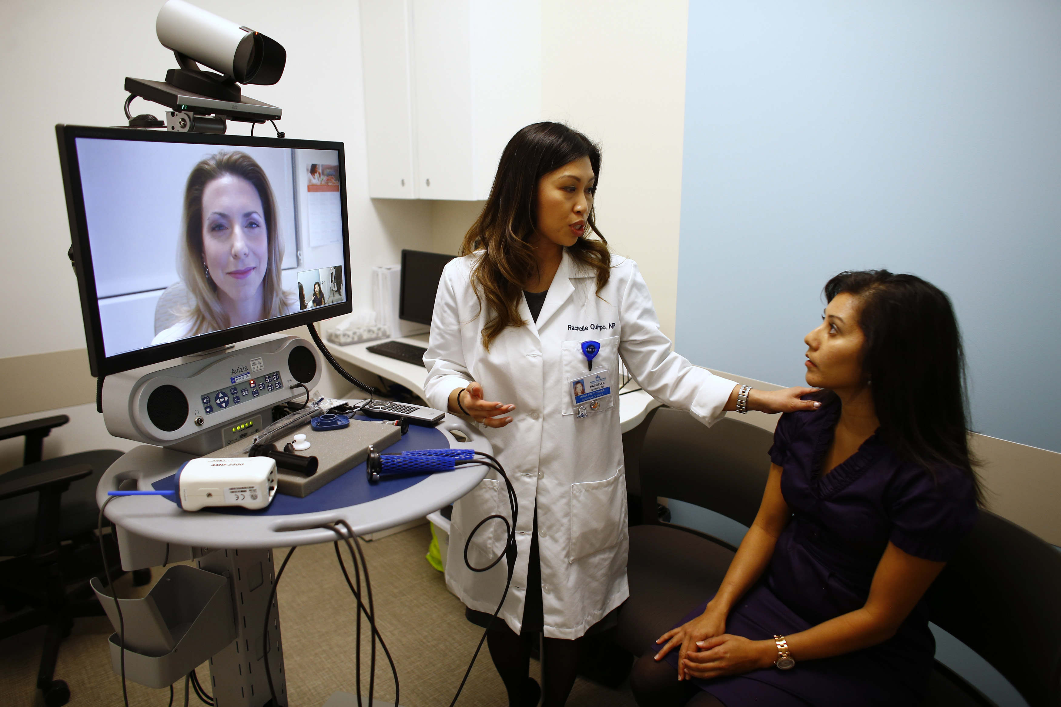 Nurse Health Practitioner Rachelle Quimpo (C) introduces patient Shreya Sasaki to Dr. Heidi Meyer, MD Family Medicine, who appears on a video screen remotely at a newly opened Kaiser Permanente health clinic inside a Target retail department store in San Diego, California November 17, 2014. Four clinics are scheduled to open in Southern California to provide pediatric and adolescent care, well-woman care, family planning, and management of chronic conditions like diabetes and high blood pressure for Kaiser members and non-members. REUTERS/Mike Blake (UNITED STATES - Tags: HEALTH BUSINESS SOCIETY)