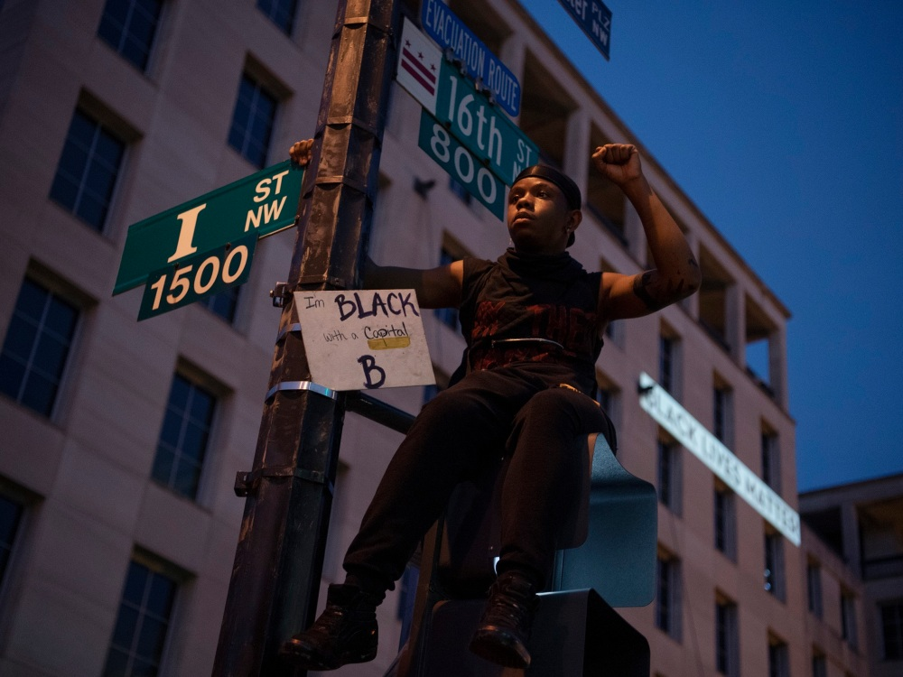 UNITED STATES - JUNE 06: A young man sits atop a street signal on the section of 16th Street dubbed Black Lives Matter Plaza after a day of demonstrations to honor George Floyd and victims of racial injustice on Saturday, June 6, 2020. (Photo By Tom Williams/CQ Roll Call/Sipa USA)No Use UK. No Use Germany.