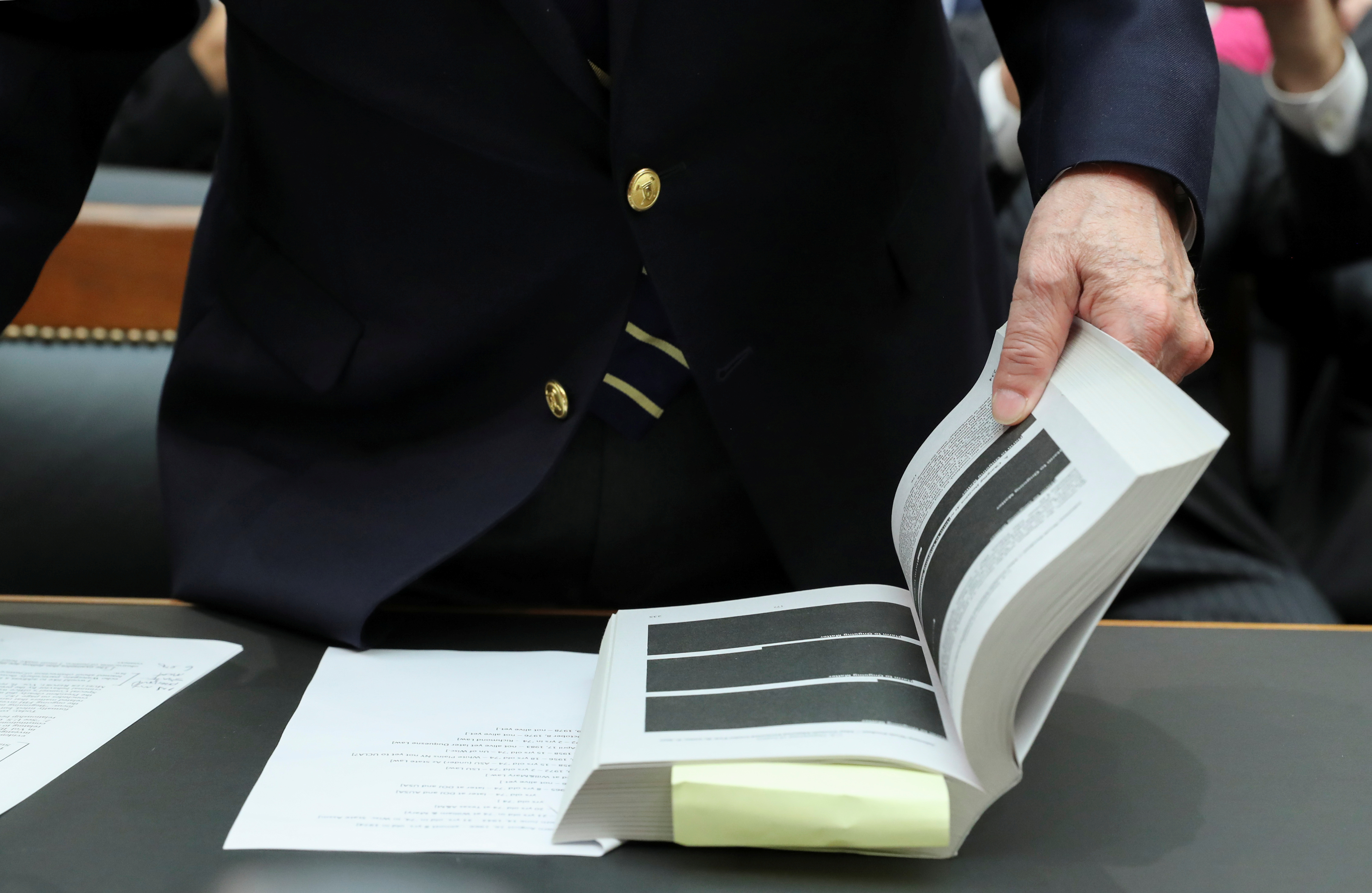 "Former White House counsel John Dean, a key figure in the Watergate scandal that toppled former President Richard Nixon, opens the report from Special Counsel Robert Mueller to a heavily redacted page as he prepares to testify before a House Judiciary Committee hearing entitled ""Lessons from the Mueller Report"" on Capitol Hill in Washington U.S., June 10, 2019.  REUTERS/Jonathan Ernst"