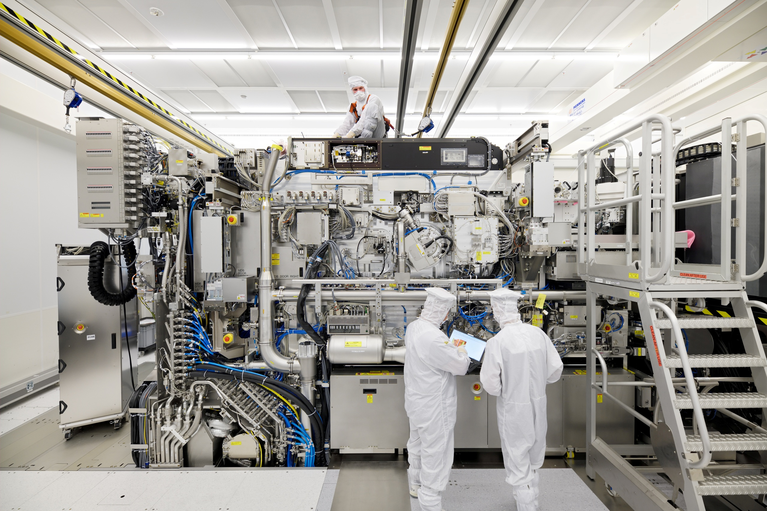 Employees are seen working on the final assembly of ASML's TWINSCAN NXE:3400B semiconductor lithography tool with its panels removed, in Veldhoven, Netherlands, in this picture taken April 4, 2019. Bart van Overbeeke Fotografie/ASML/Handout via REUTERS ATTENTION EDITORS - THIS IMAGE HAS BEEN SUPPLIED BY A THIRD PARTY. MANDATORY CREDIT.