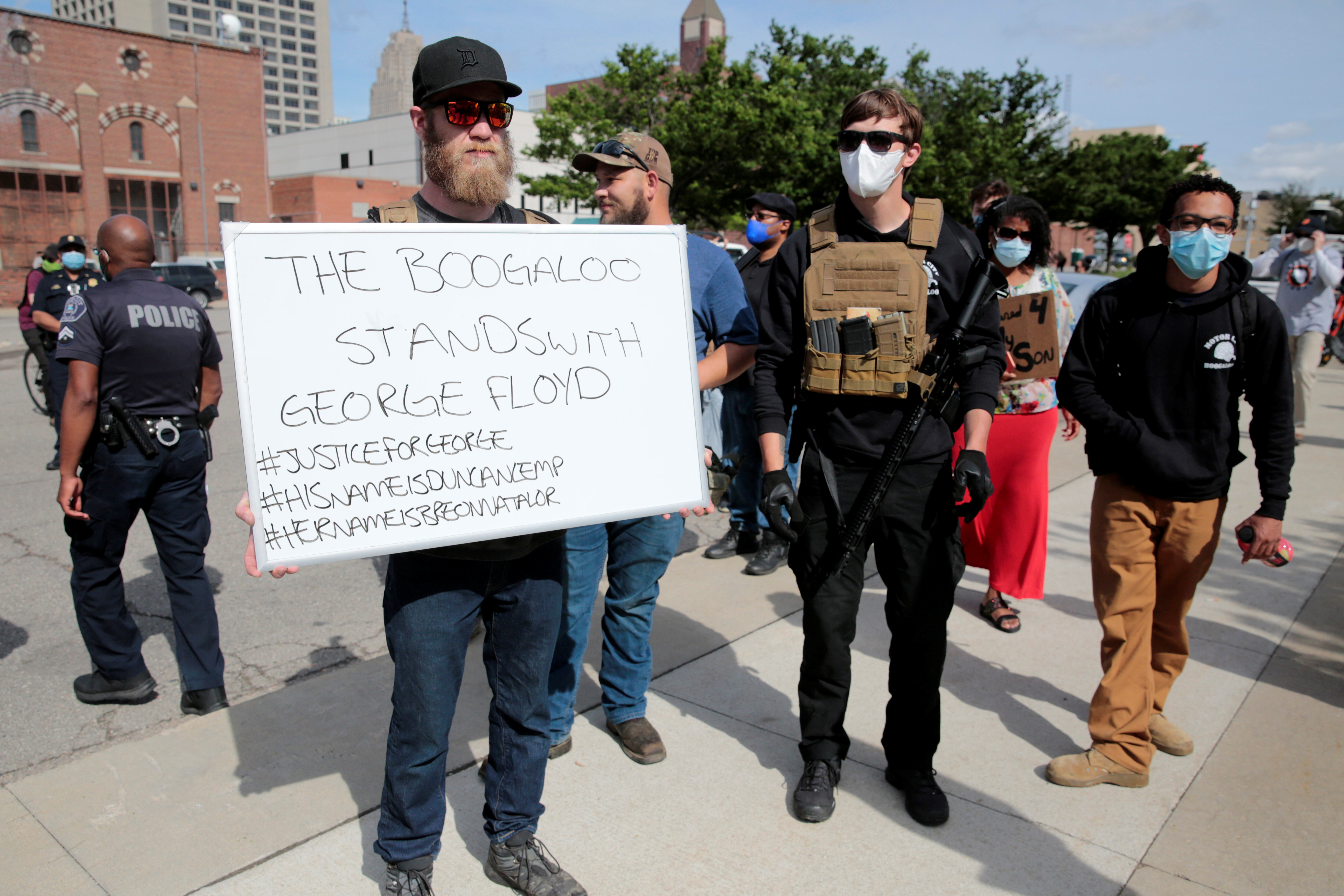 """Armed men, one carrying a """"The Boogaloo stands with George Floyd"""" sign, are seen as protesters rally against the death in Minneapolis police custody of George Floyd, in Detroit, Michigan, U.S. May 30, 2020. Picture taken May 30, 2020.   REUTERS/Rebecca Cook"""