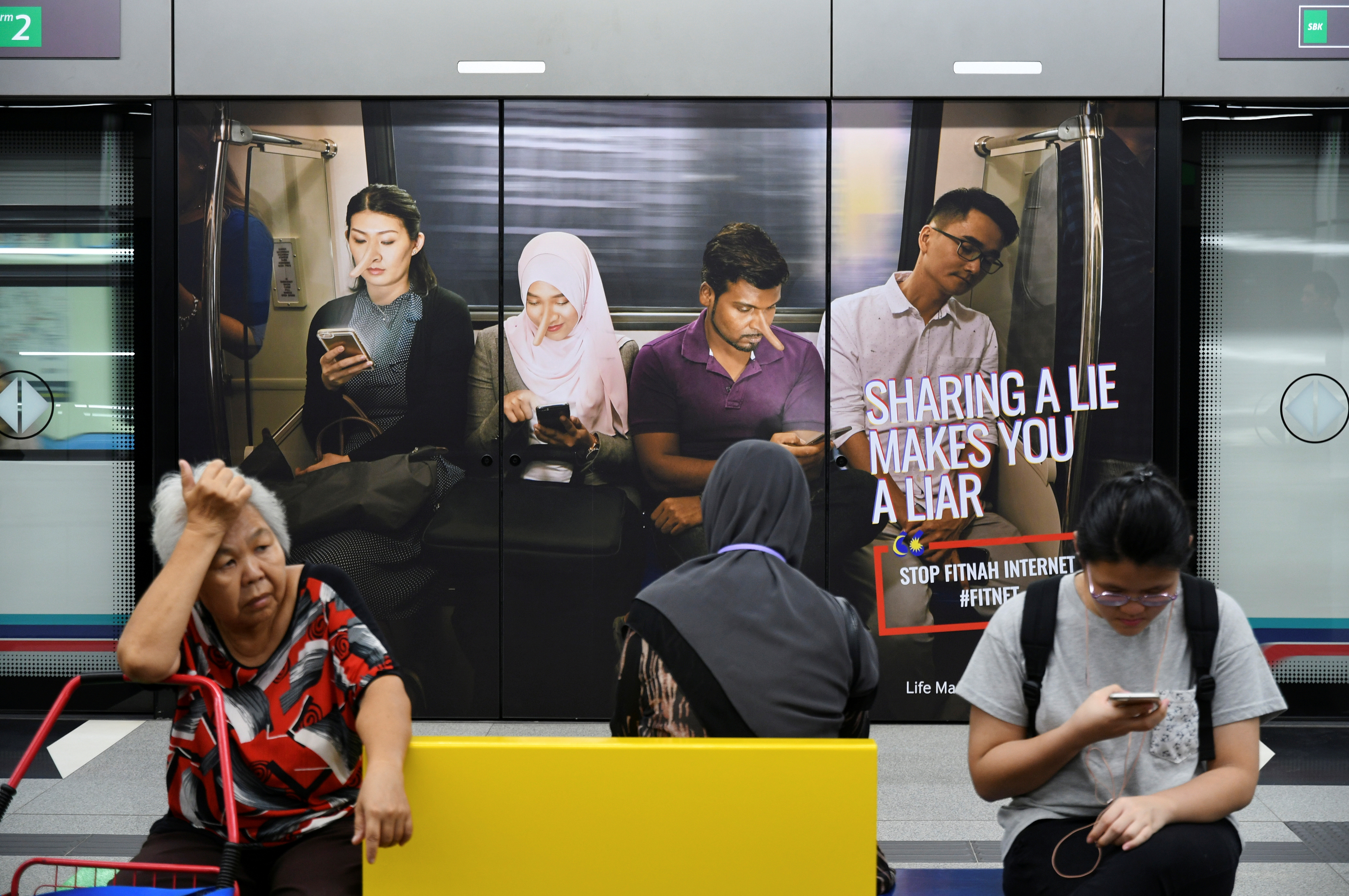 Commuters sit in front of an advertisement discouraging the dissemination of fake news, at a train station in Kuala Lumpur, Malaysia March 28, 2018. Picture taken March 28, 2018. REUTERS/Stringer