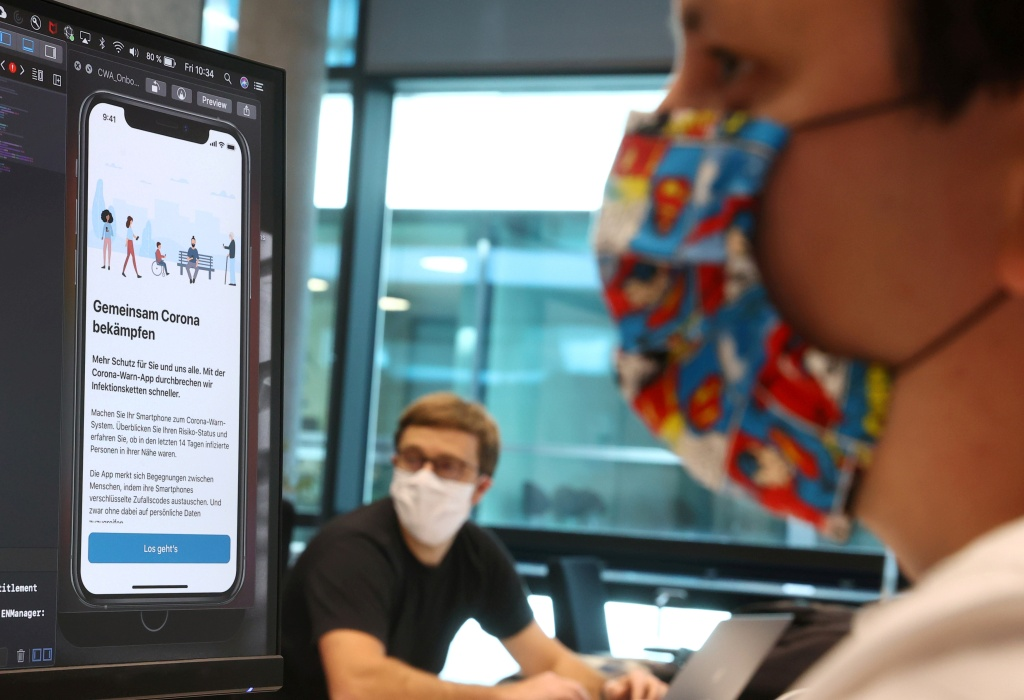FILE PHOTO: Florian Heretsch and Emil Voutta of the developing team of software giant SAP work on the German government official COVID-19 tracing App at the SAP headquarters, as the spread of the coronavirus disease (COVID-19) continues, in Walldorf, Germany May 29, 2020. REUTERS/Kai Pfaffenbach/File Photo