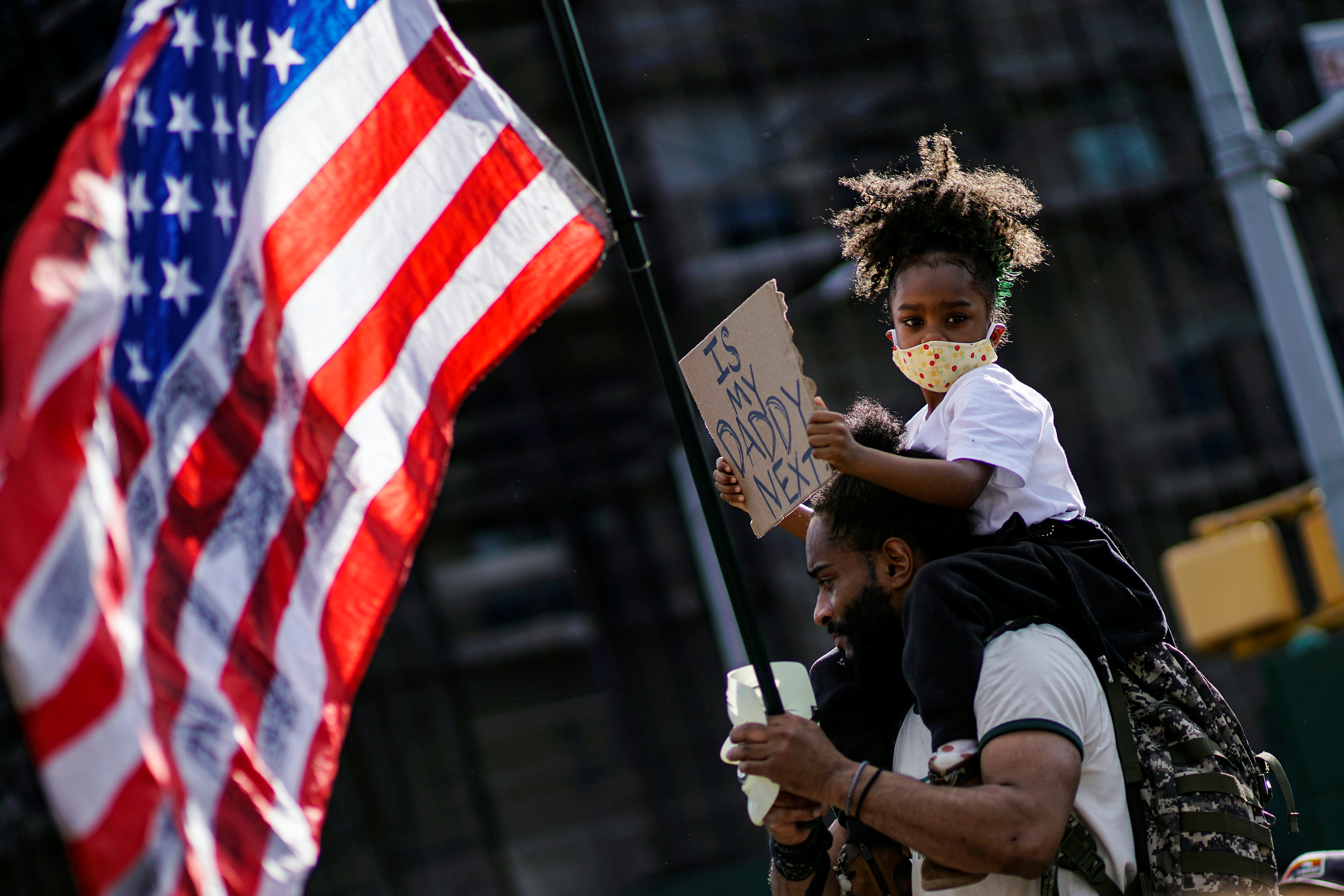 A child looks on with a sign while her father carries a U.S. flag during a protest against racial inequality in the aftermath of the death in Minneapolis police custody of George Floyd, in front of the at Grand Army Plaza in the Brooklyn borough of New York City, New York, U.S. June 7, 2020. REUTERS/Eduardo Munoz