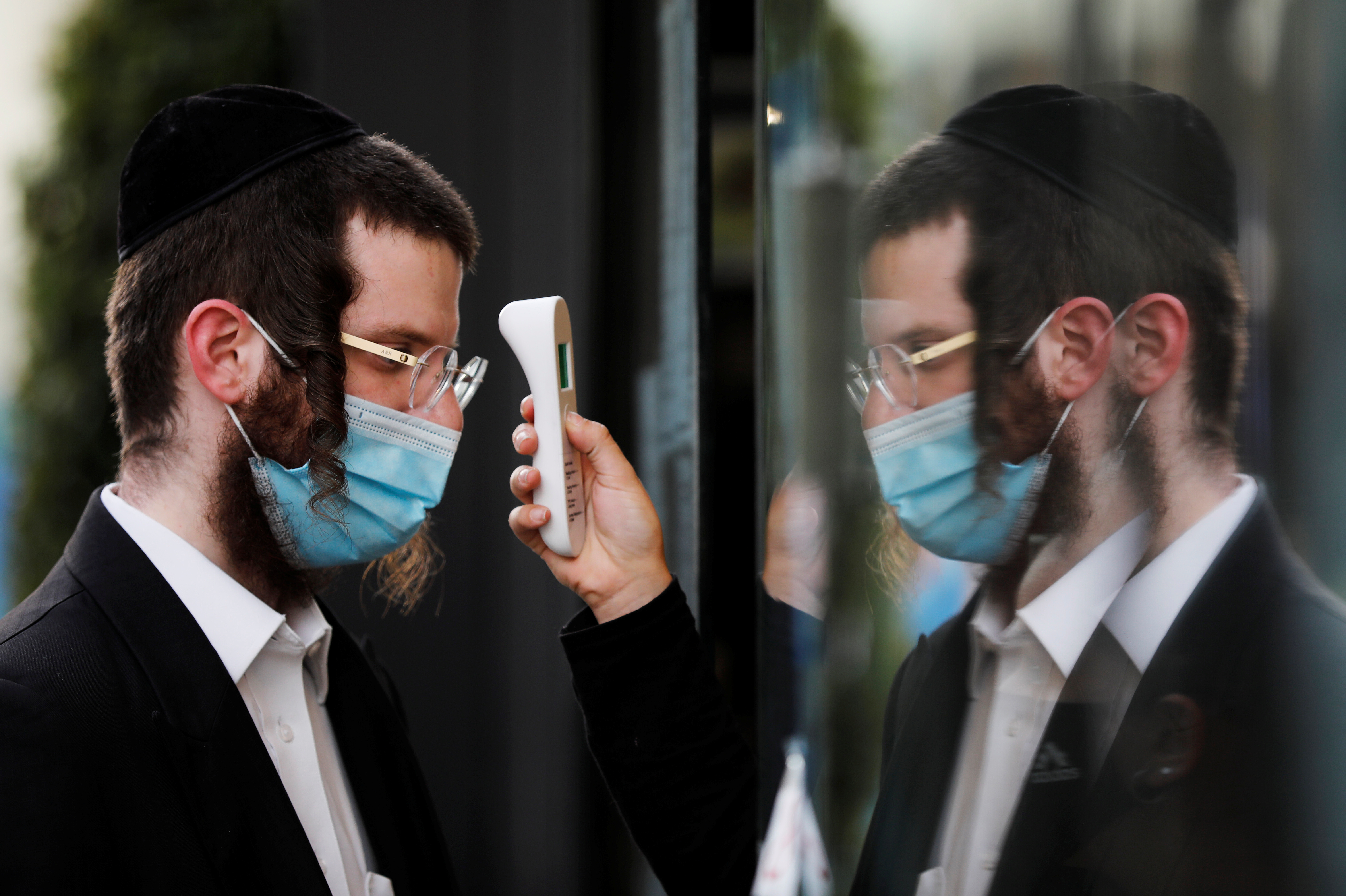 A visitor gets his temperature measured as he wears a face mask at a fashion shopping center in Ashdod, as restrictions over the coronavirus disease (COVID-19) ease around Israel, May 5, 2020. REUTERS/Amir Cohen