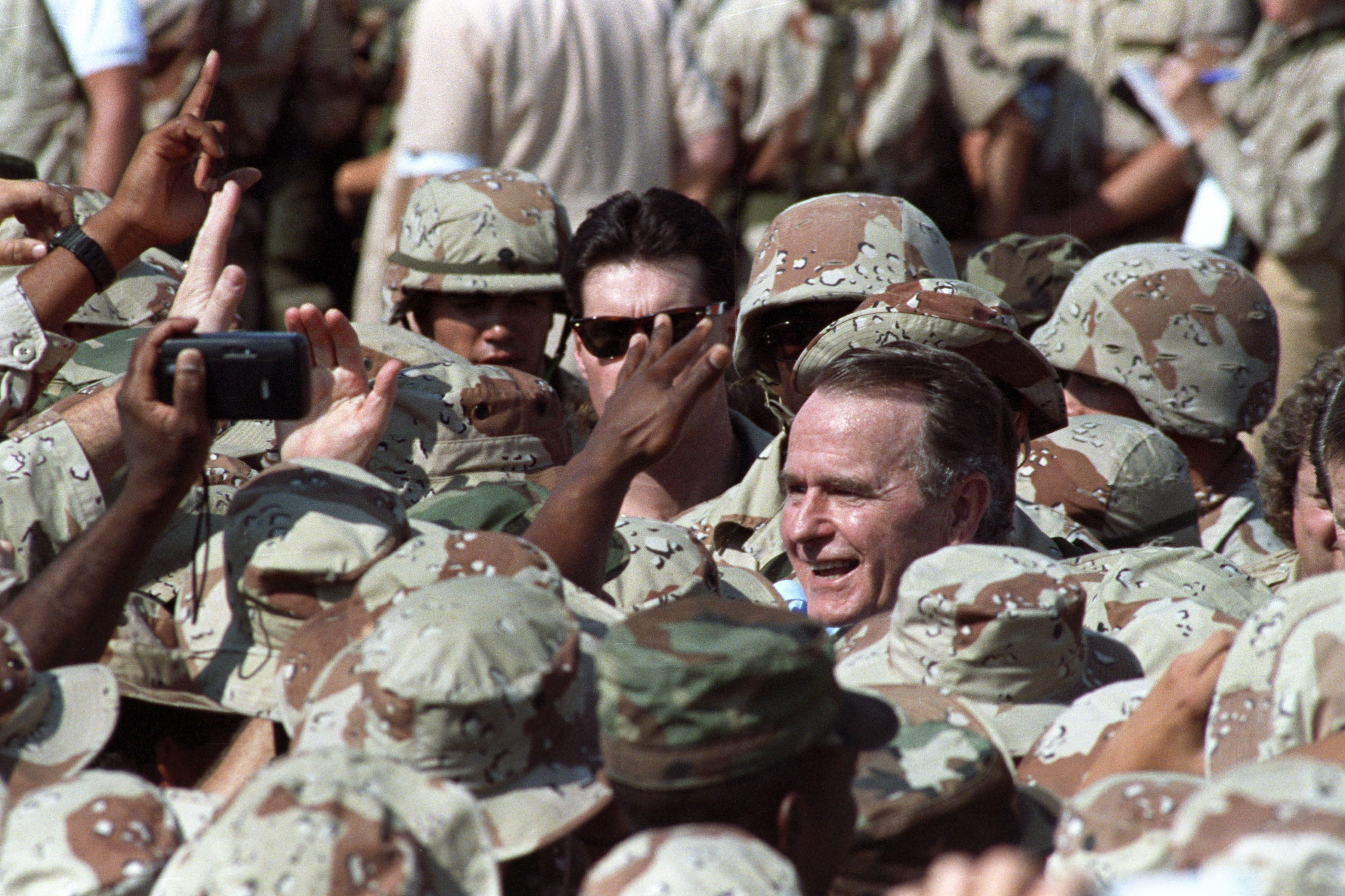 President George H.W. Bush is surrounded by a sea of U.S. military personnel as he greets troops following an arrival ceremony in the eastern Saudi Arabian city of Dhahran November 22, 1990. Bush celebrates Thanksgiving Day with U.S. troops from all branches of the military deployed here after the Iraqi invasion of Kuwait.   Reuters/Terry Bochatey ( SAUDI ARABIA - Tags: POLITICS CIVIL UNREST) BEST QUALITY AVAILABLE