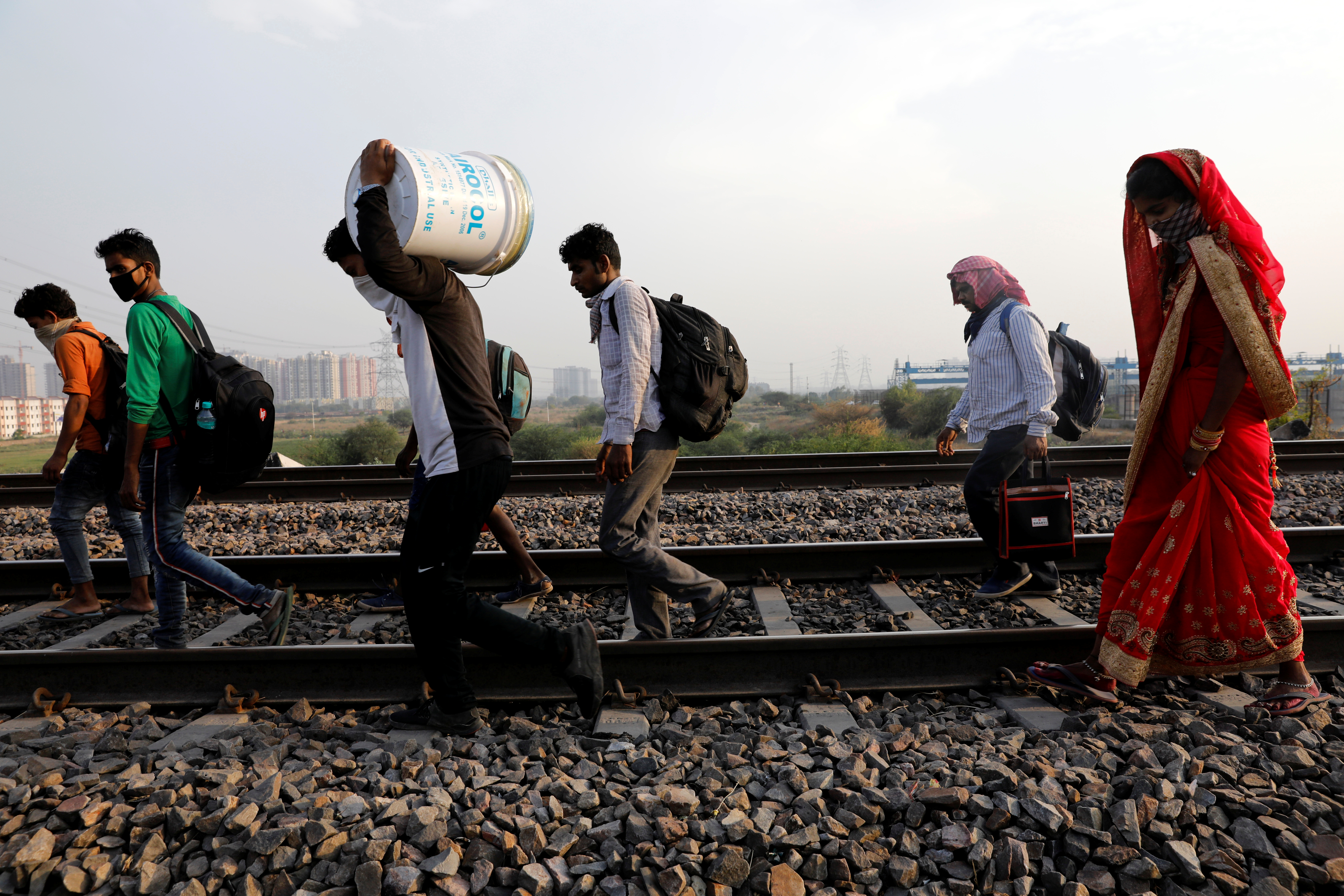 Migrant workers with their faces covered and carrying their belongings, walk along a railway track to return to their home state of eastern Bihar, during an extended nationwide lockdown to slow the spread of the coronavirus disease (COVID-19), in Ghaziabad, in the outskirts of New Delhi, India, May 13, 2020. REUTERS/Adnan Abidi