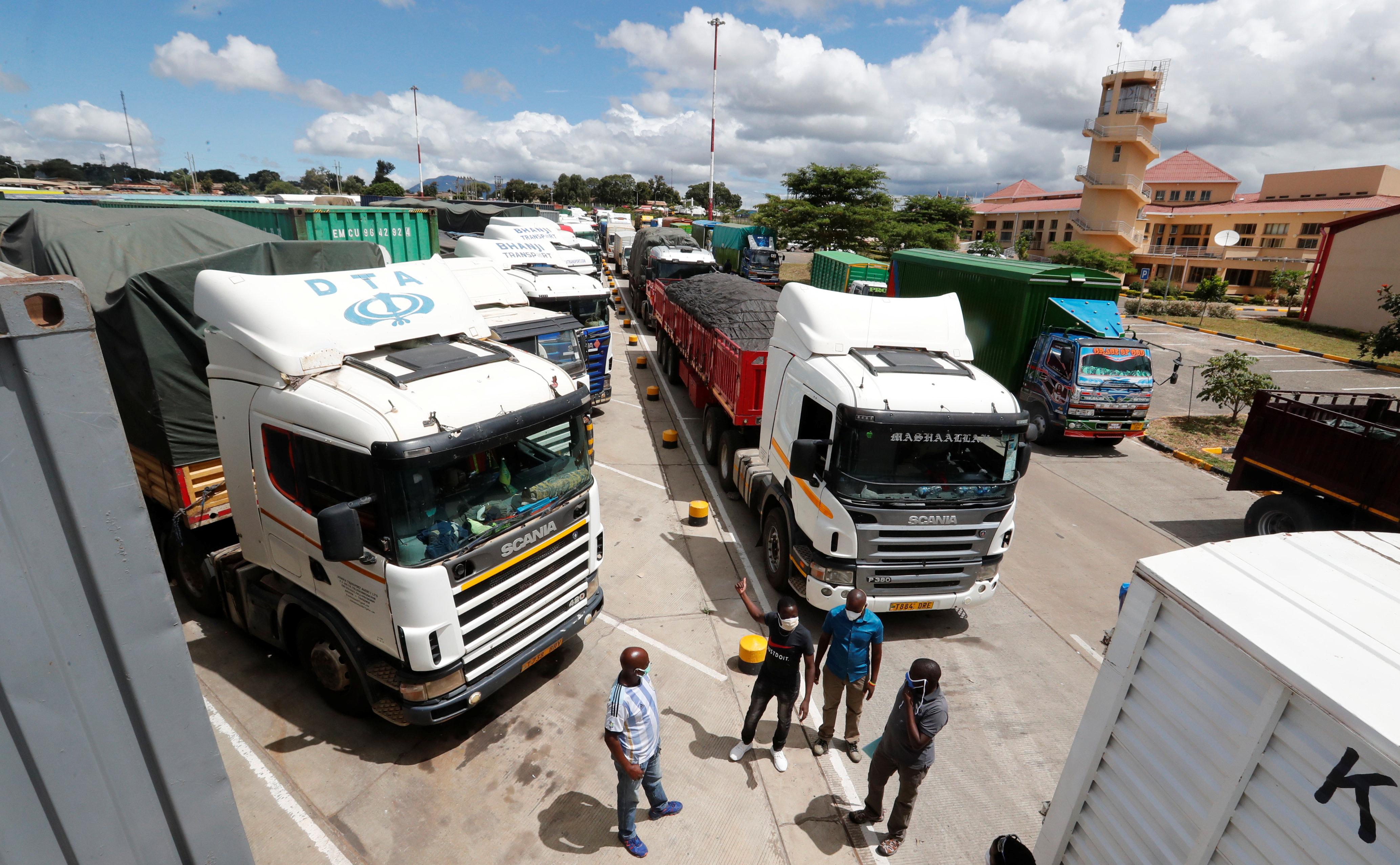 Truck drivers wait near their parked vehicles for the coronavirus disease (COVID-19) test results at the Namanga one stop border crossing point between Kenya and Tanzania, in Namanga, Kenya May 12, 2020. REUTERS/Thomas Mukoya