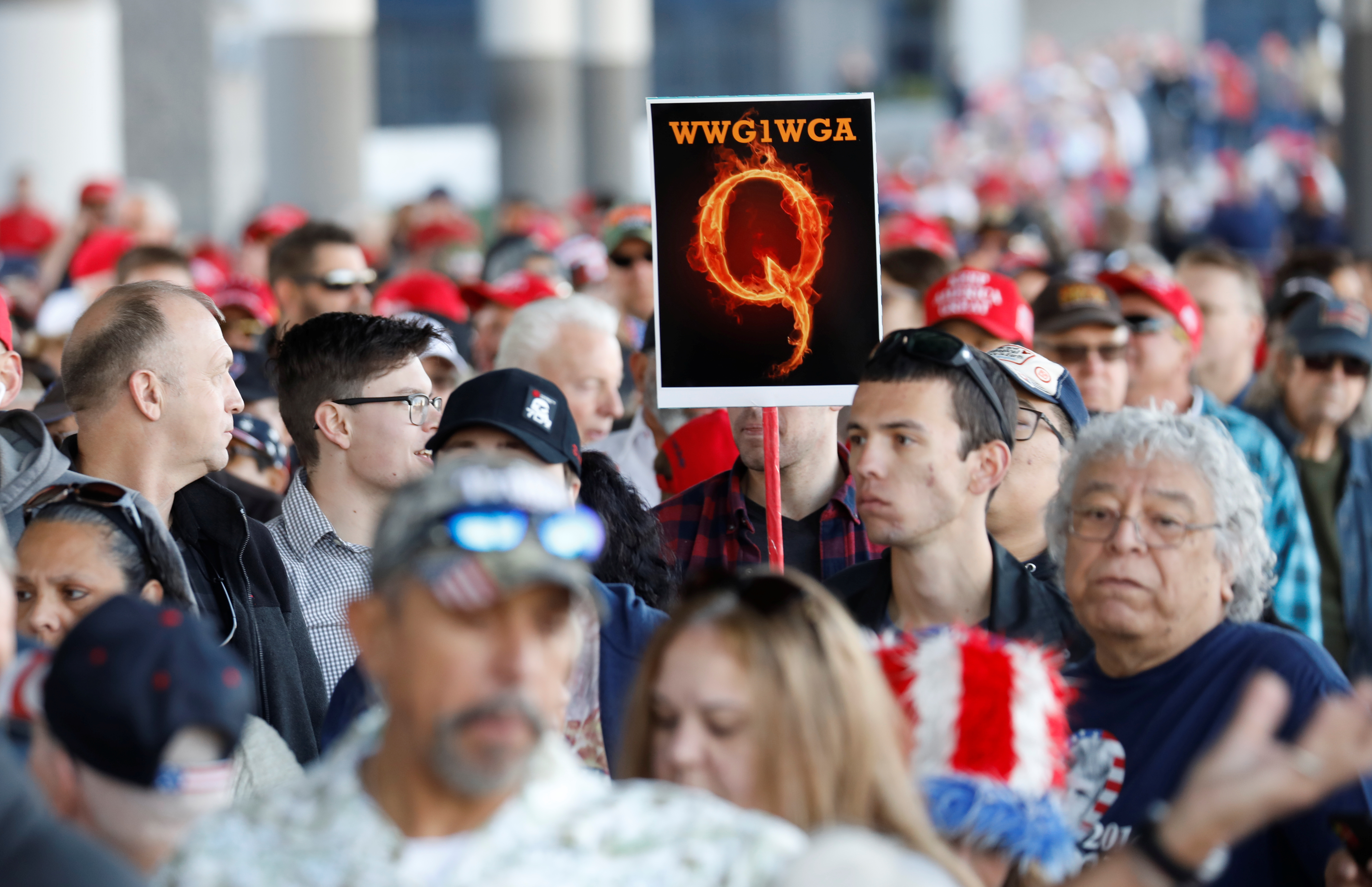 "A man in the crowd holds a QAnon sign with the group's abbreviation of their rallying cry ""Where we go one, we go all"" as crowds gather to attend U.S. President Donald Trump's campaign rally at the Las Vegas Convention Center in Las Vegas, Nevada, U.S., February 21, 2020. REUTERS/Patrick Fallon"