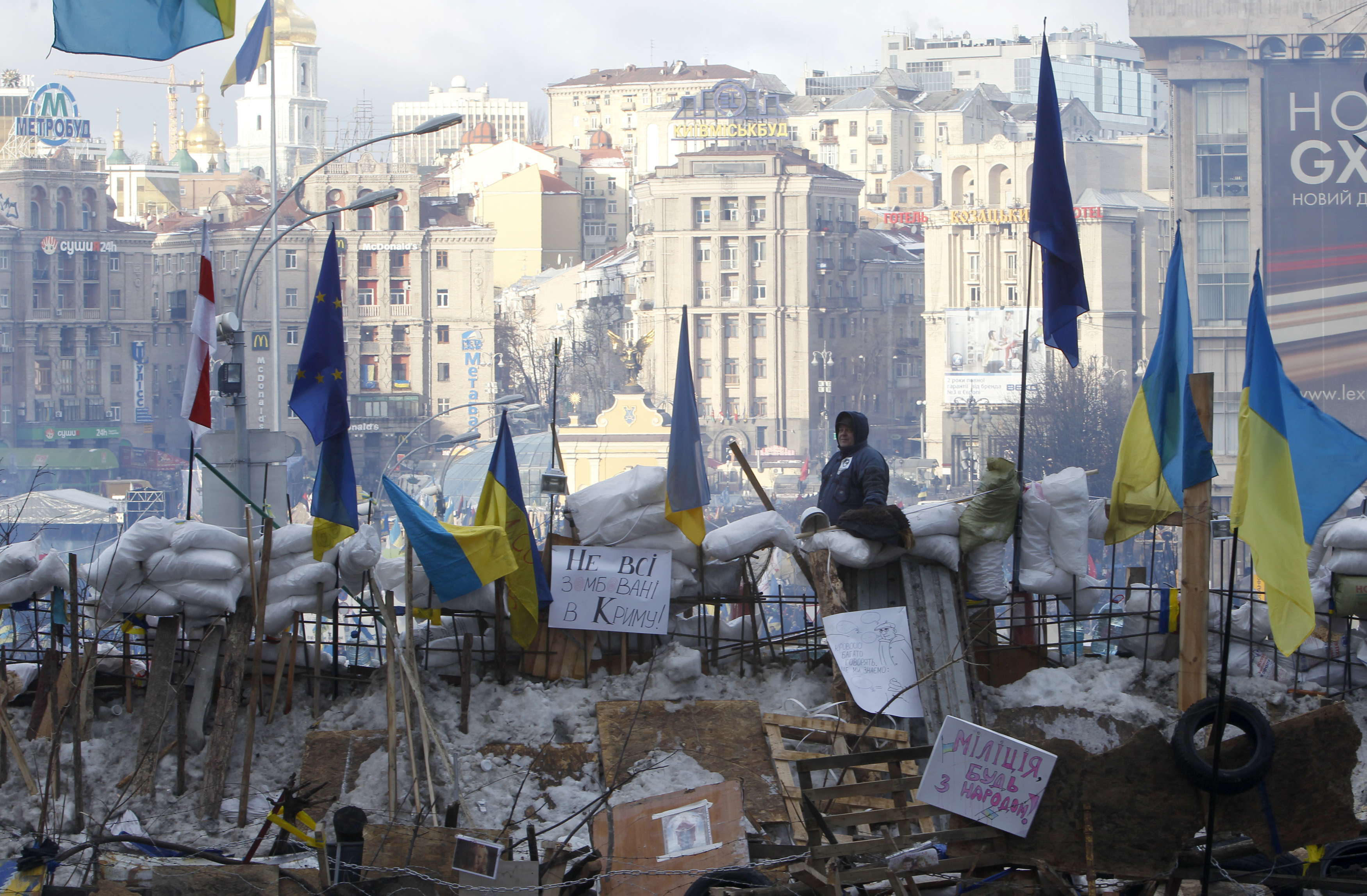 A pro-European integration protester looks out from a barricade on Independence Square in Kiev December 14, 2013. Ukrainian President Viktor Yanukovich made few concessions on Friday in crisis talks with the opposition, his first direct attempt to defuse weeks of unrest over a policy swerve to Russia away from Europe.   REUTERS/Vasily Fedosenko (UKRAINE - Tags: POLITICS CIVIL UNREST)