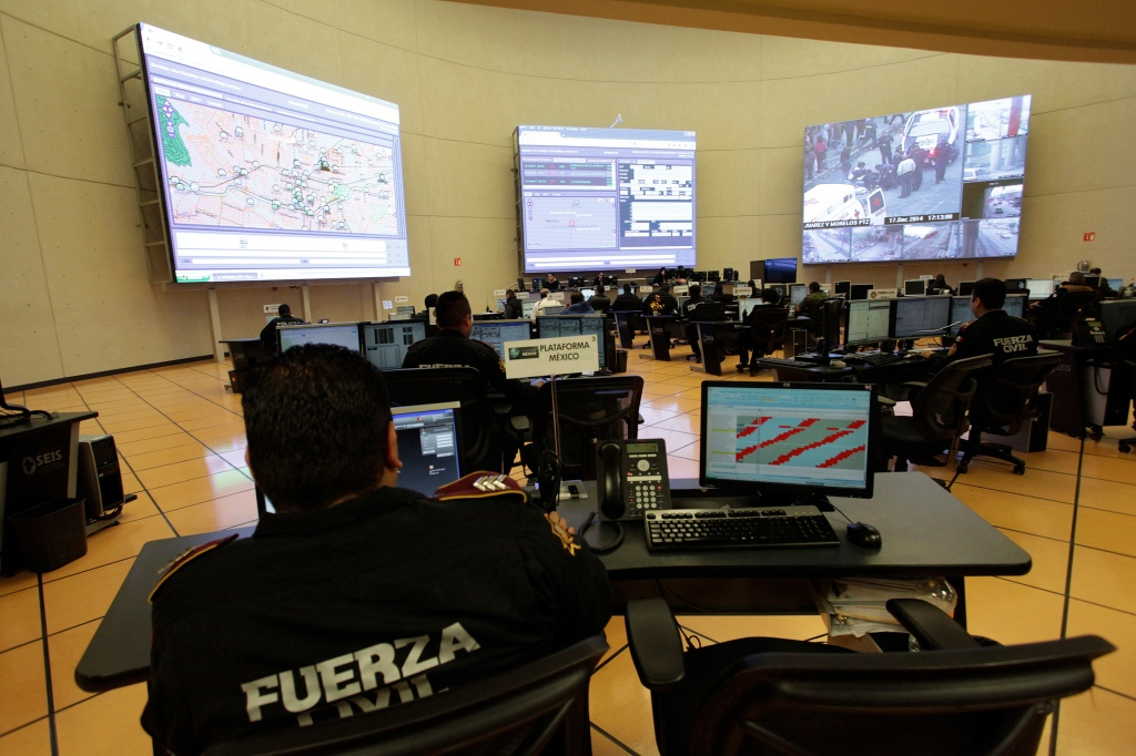Police officers in Mexico monitor feeds from surveillance cameras displayed on several large monitors.