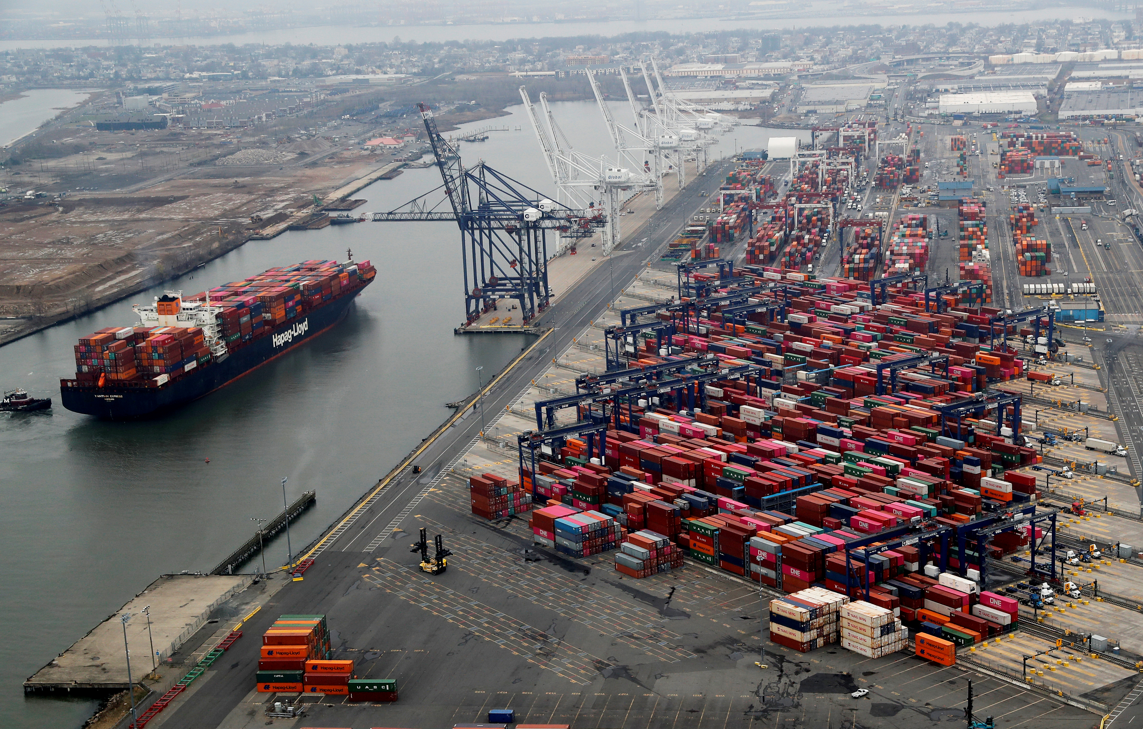 A container ship is seen as hundreds of shipping containers are seen stacked at a pier at the Port of New York and New Jersey in Elizabeth, New Jersey, U.S., March 30, 2020. REUTERS/Mike Segar
