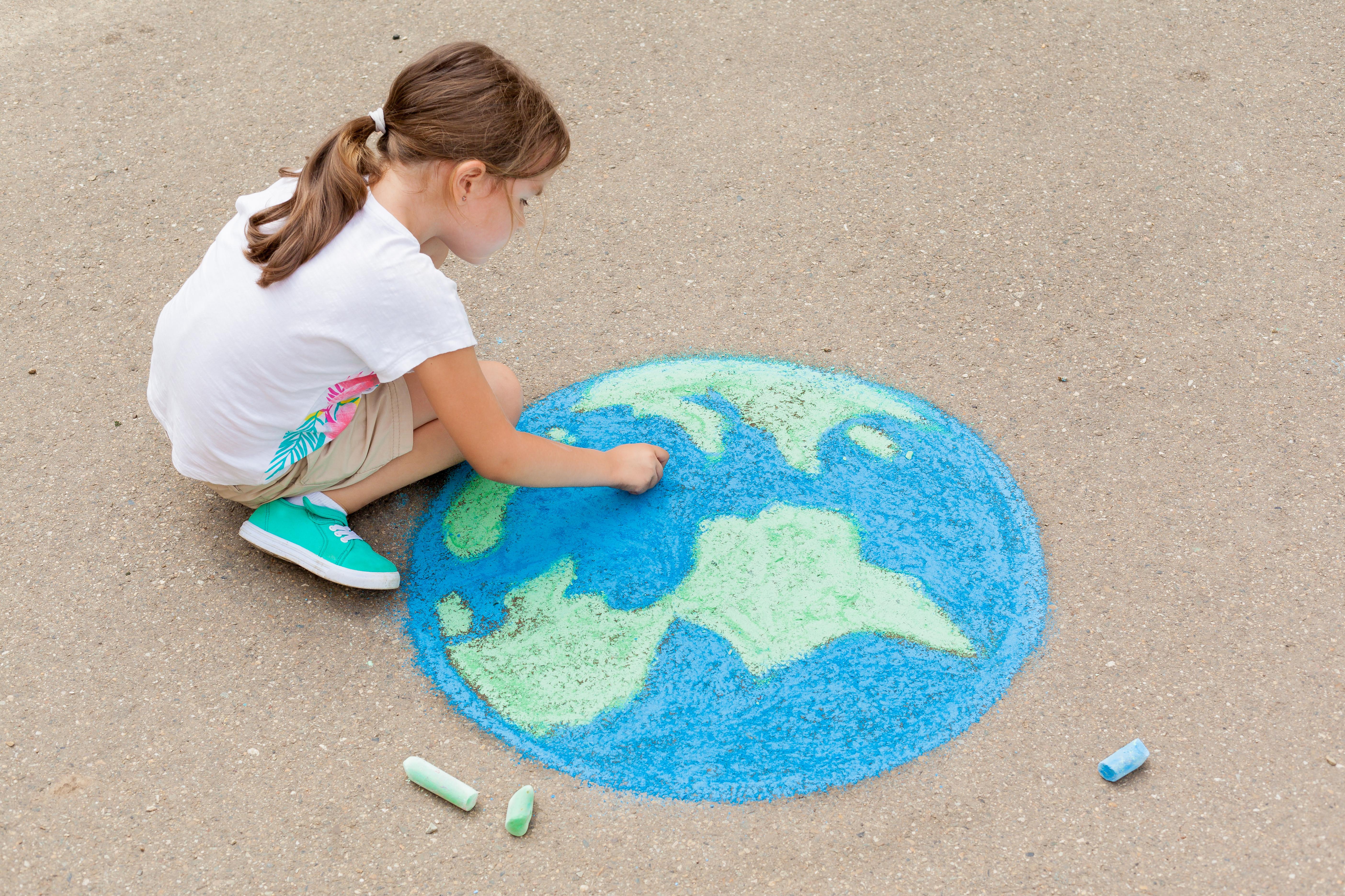 Girl draws the Earth using chalk