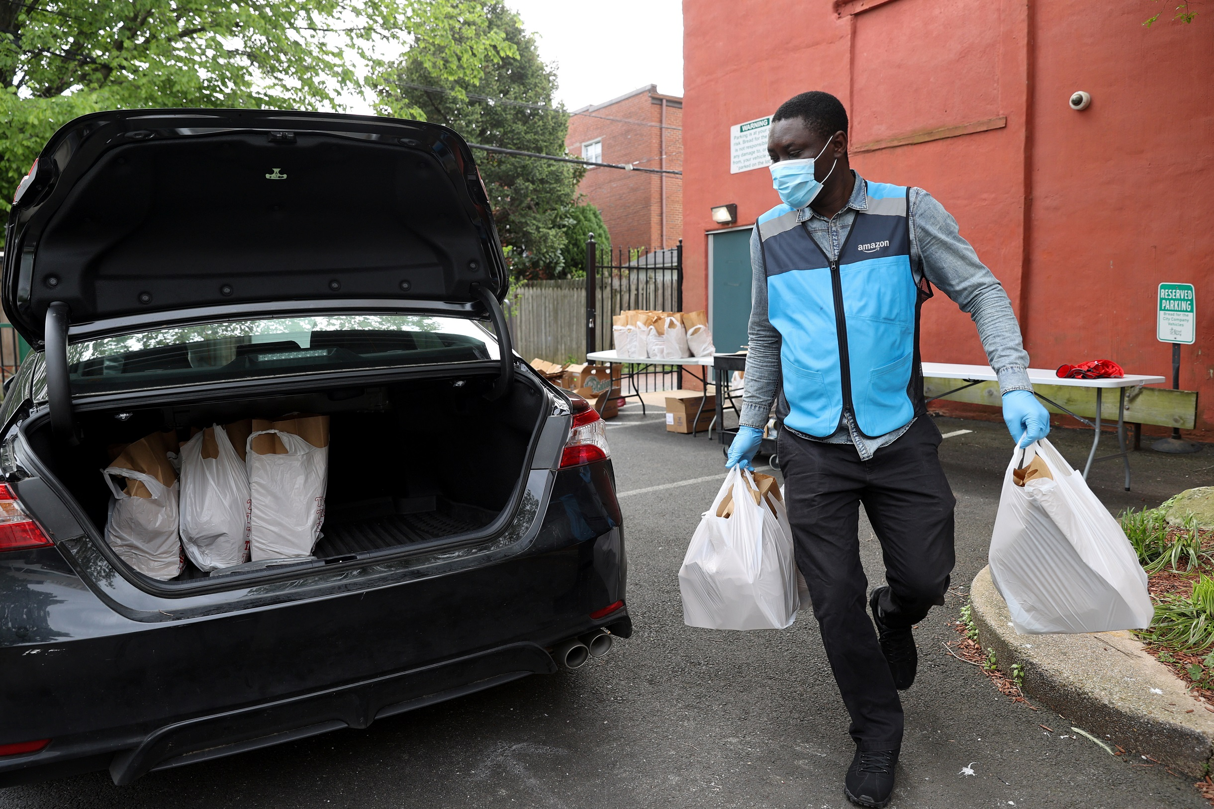 Contract drivers paid by Amazon, including Ayodeji Akinsanya, collect bags of free groceries to deliver from the Bread for the City social services charity during the coronavirus disease (COVID-19) outbreak, in Washington, U.S. May 5, 2020. The charity is sending out as many as 500 or 600 bags a day using the drivers. REUTERS/Jonathan Ernst