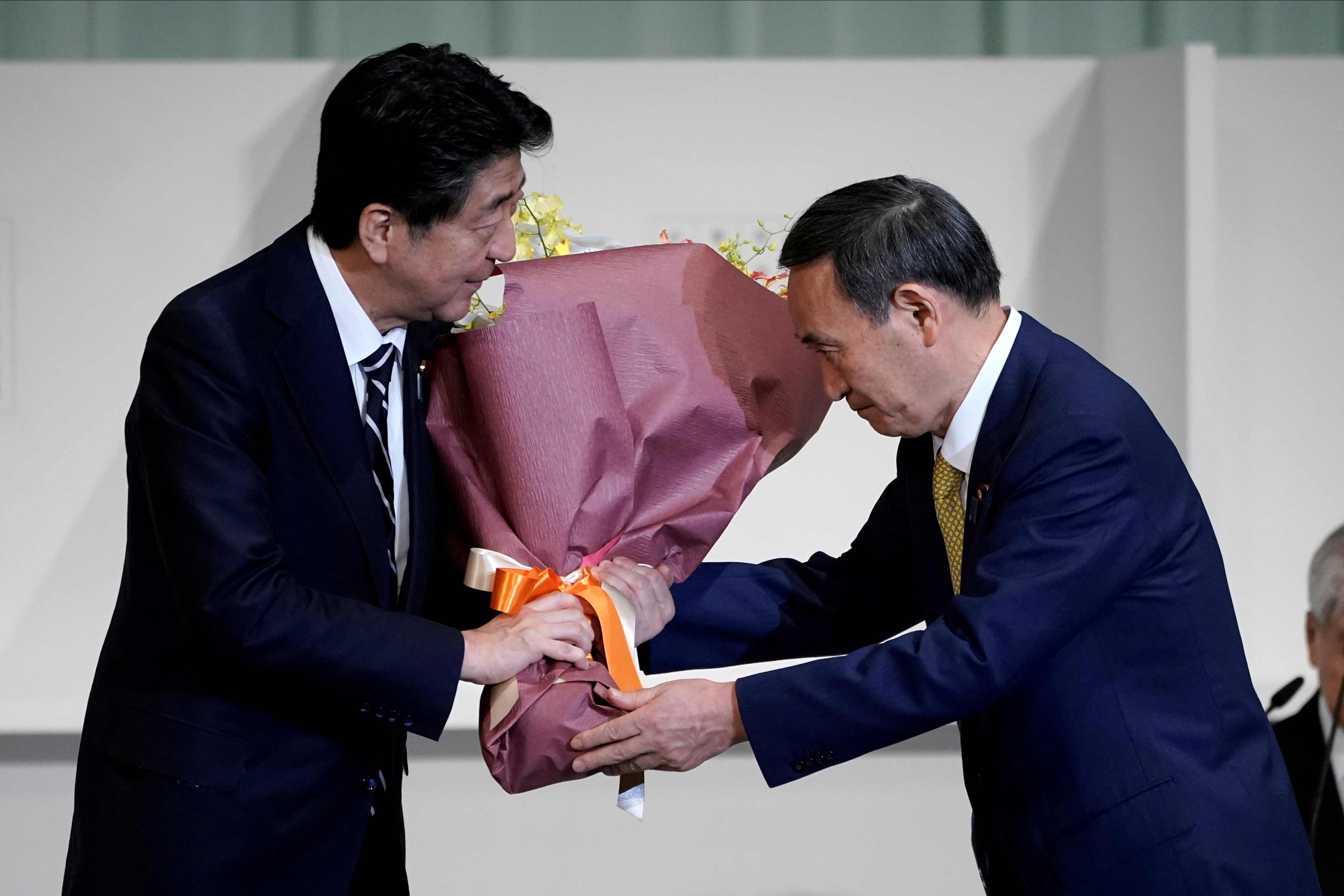 Japan's Chief Cabinet Secretary Yoshihide Suga presents Prime Minister Shinzo Abe with flowers after Suga was elected as new head of the ruling party at the Liberal Democratic Party's (LDP) leadership election in Tokyo, Japan September 14, 2020. Eugene Hoshiko/Pool via REUTERS REFILE - CORRECTING FLOWERS RECIPIENT
