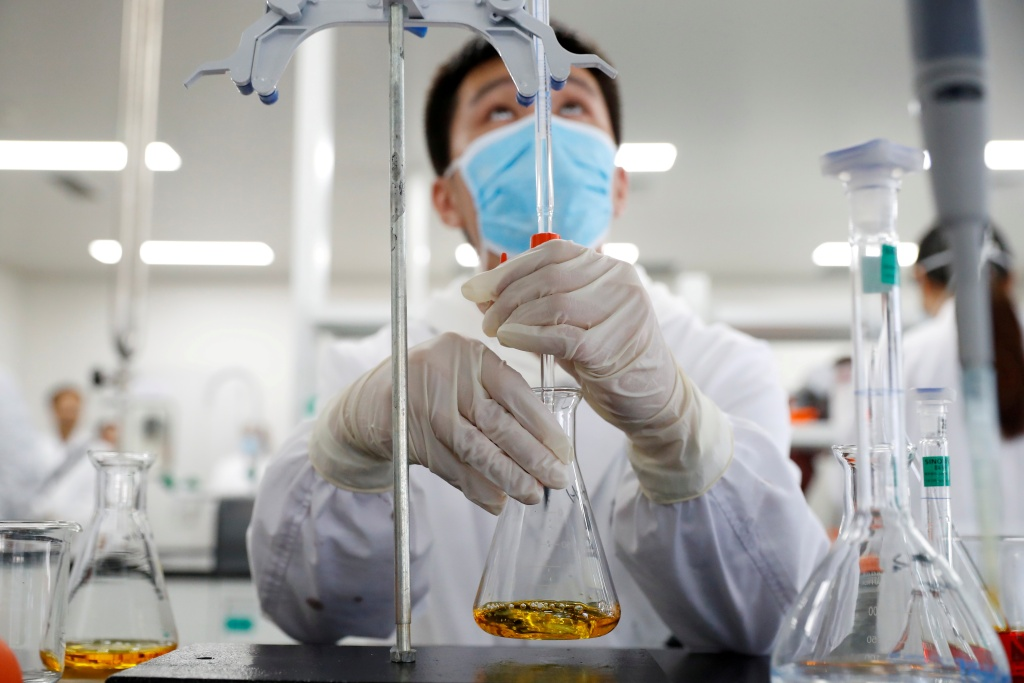 A man wearing gloves and a mask works in a Chinese lab developing an experimental COVID-19 vaccine.