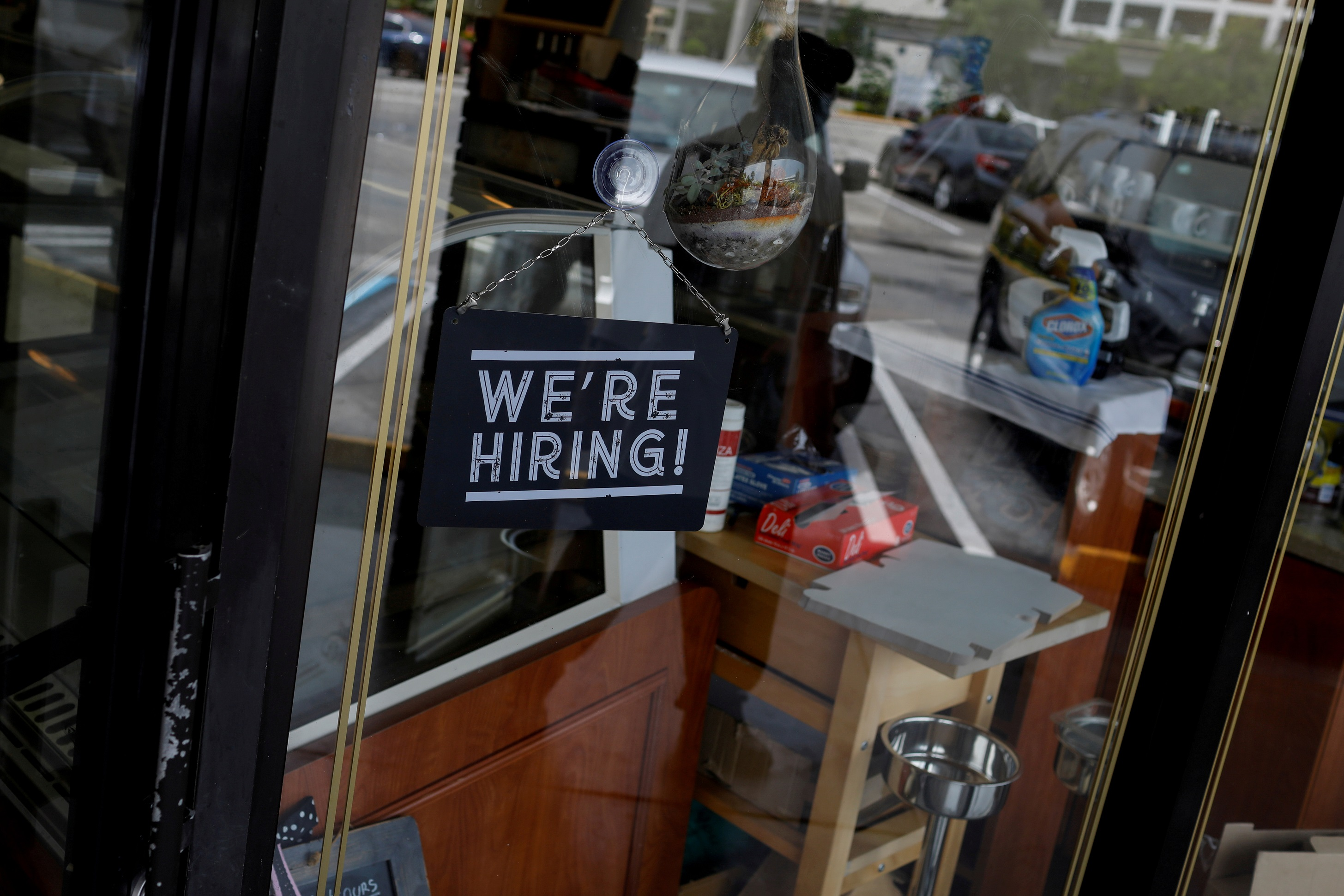 """FILE PHOTO: A """"We're Hiring"""" sign advertising jobs is seen at the entrance of a restaurant in Miami, Florida, U.S., May 18, 2020. REUTERS/Marco Bello/File Photo"""