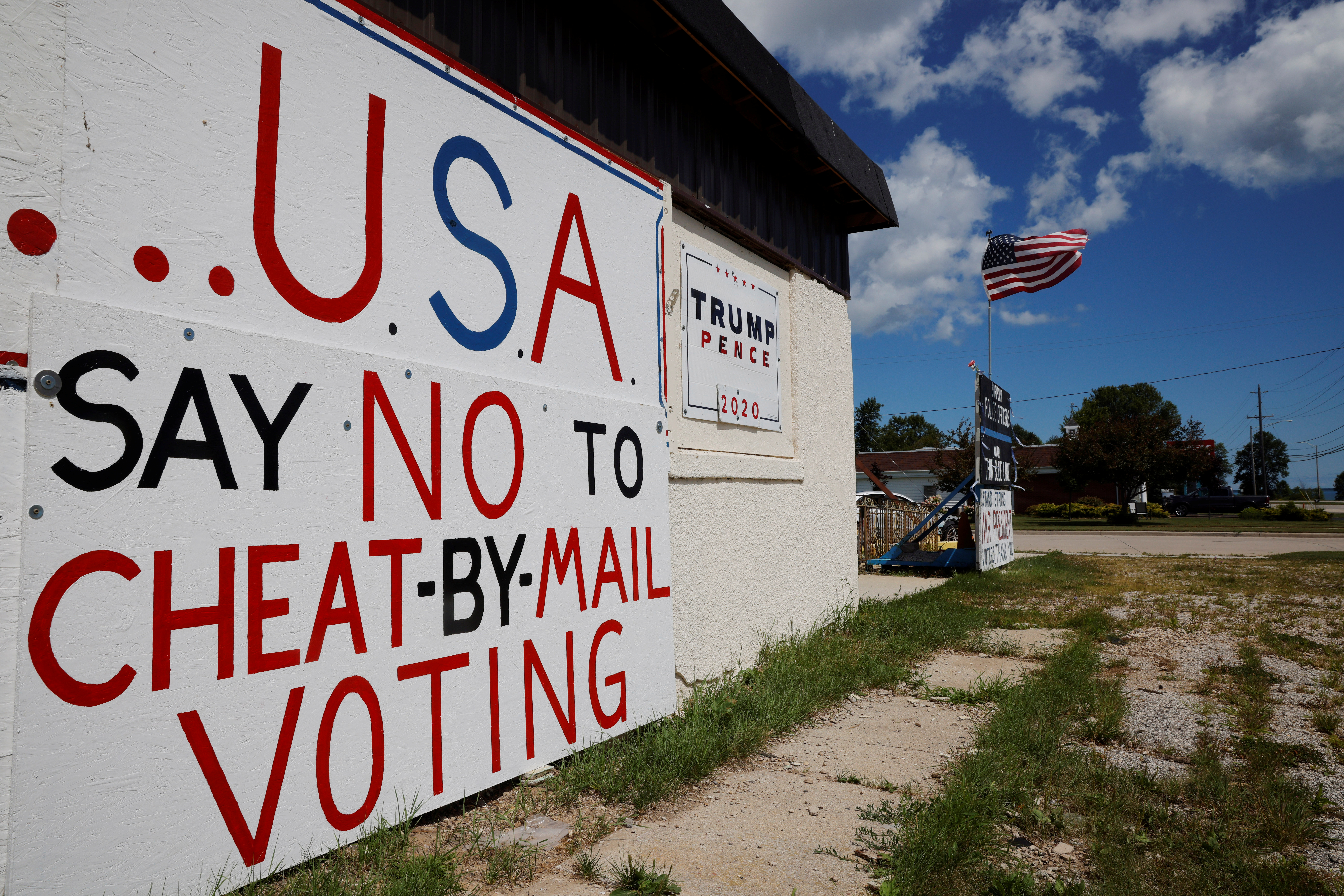 Handmade signs supporting U.S. President Donald Trump, including one opposing mail-in voting, stand outside a business in Manitowoc, Wisconsin, U.S., August 18, 2020. REUTERS/Brian Snyder