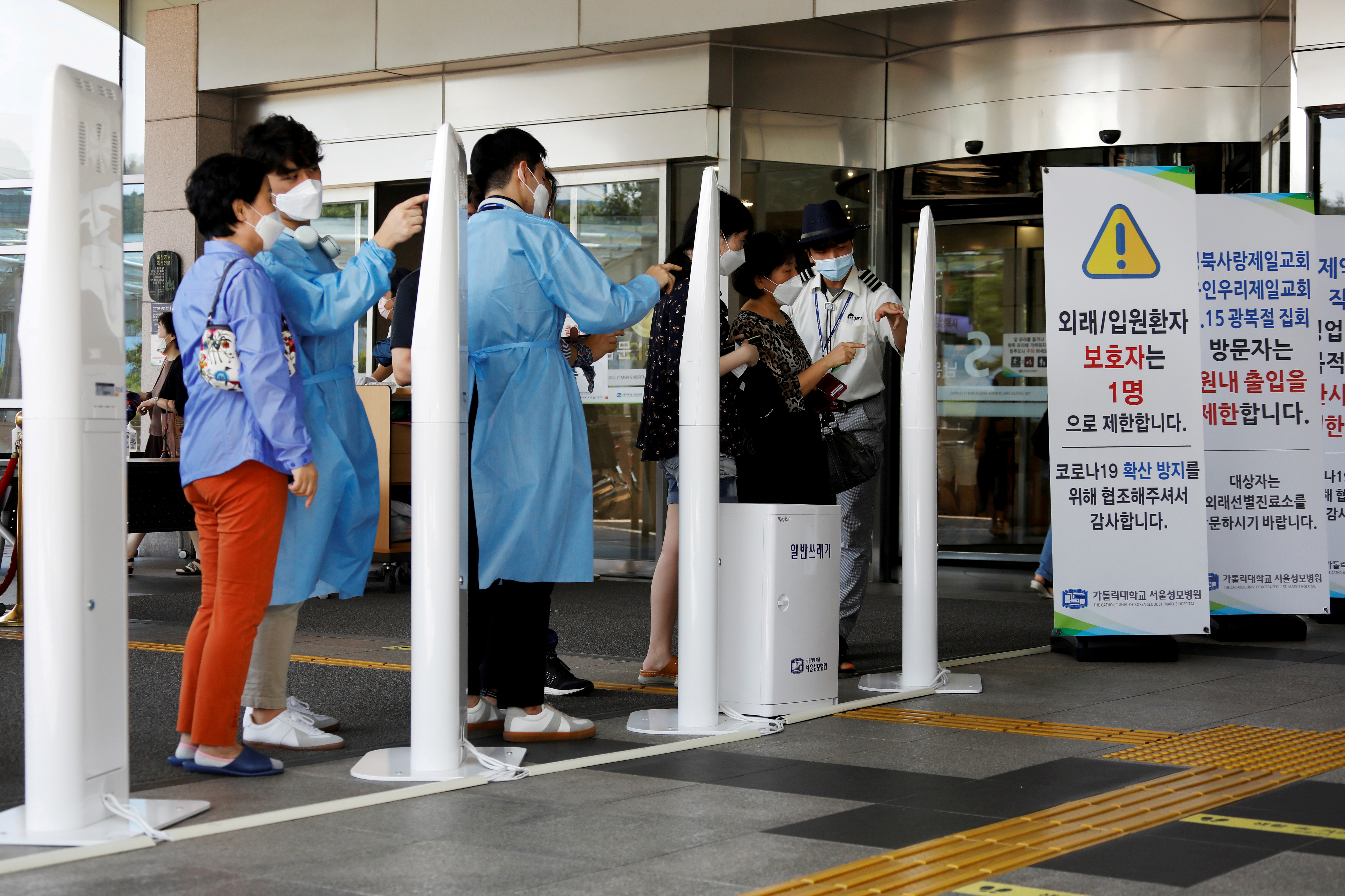 FILE PHOTO: FILE PHOTO: Visitors wearing masks to avoid the spread of COVID-19 fill out a form which is mandatory to get into a hospital in Seoul, South Korea, August 26, 2020.  REUTERS/Kim Hong-Ji