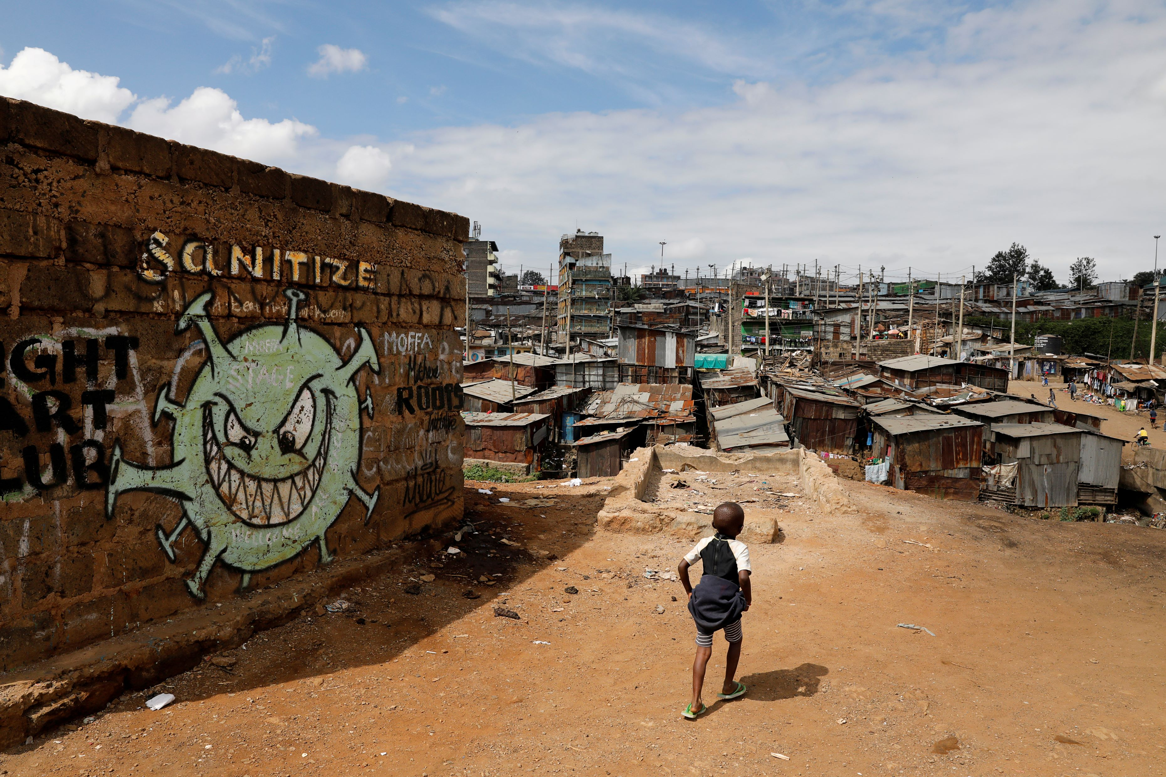 A boy walks in front of a graffiti promoting the fight against the coronavirus disease (COVID-19) in the Mathare slums of Nairobi, Kenya, May 22, 2020. REUTERS/Baz Ratner TPX IMAGES OF THE DAY