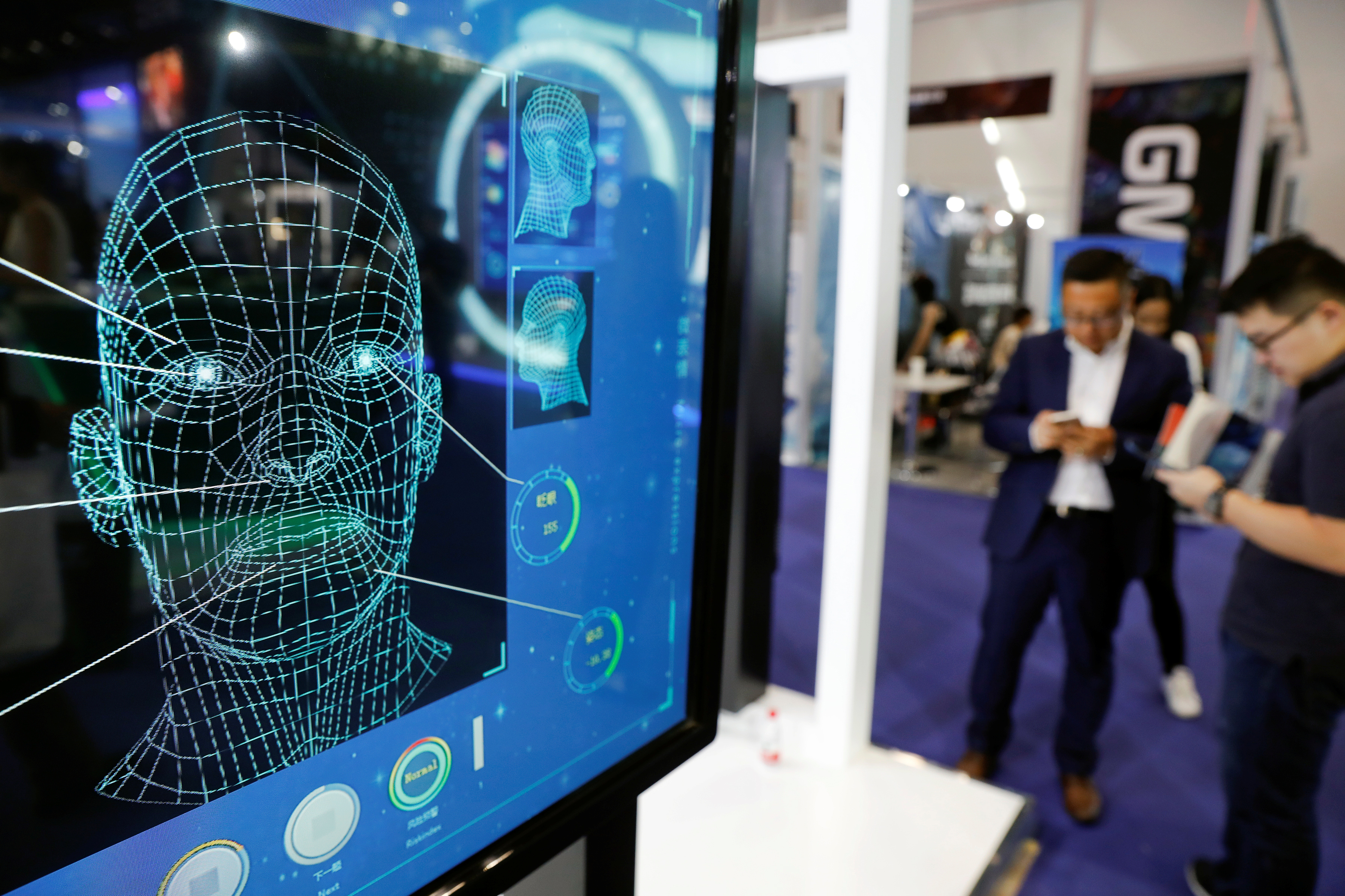 Visitors check their phones behind the screen advertising facial recognition software during Global Mobile Internet Conference (GMIC) at the National Convention in Beijing, China April 27, 2018. REUTERS/Damir Sagolj