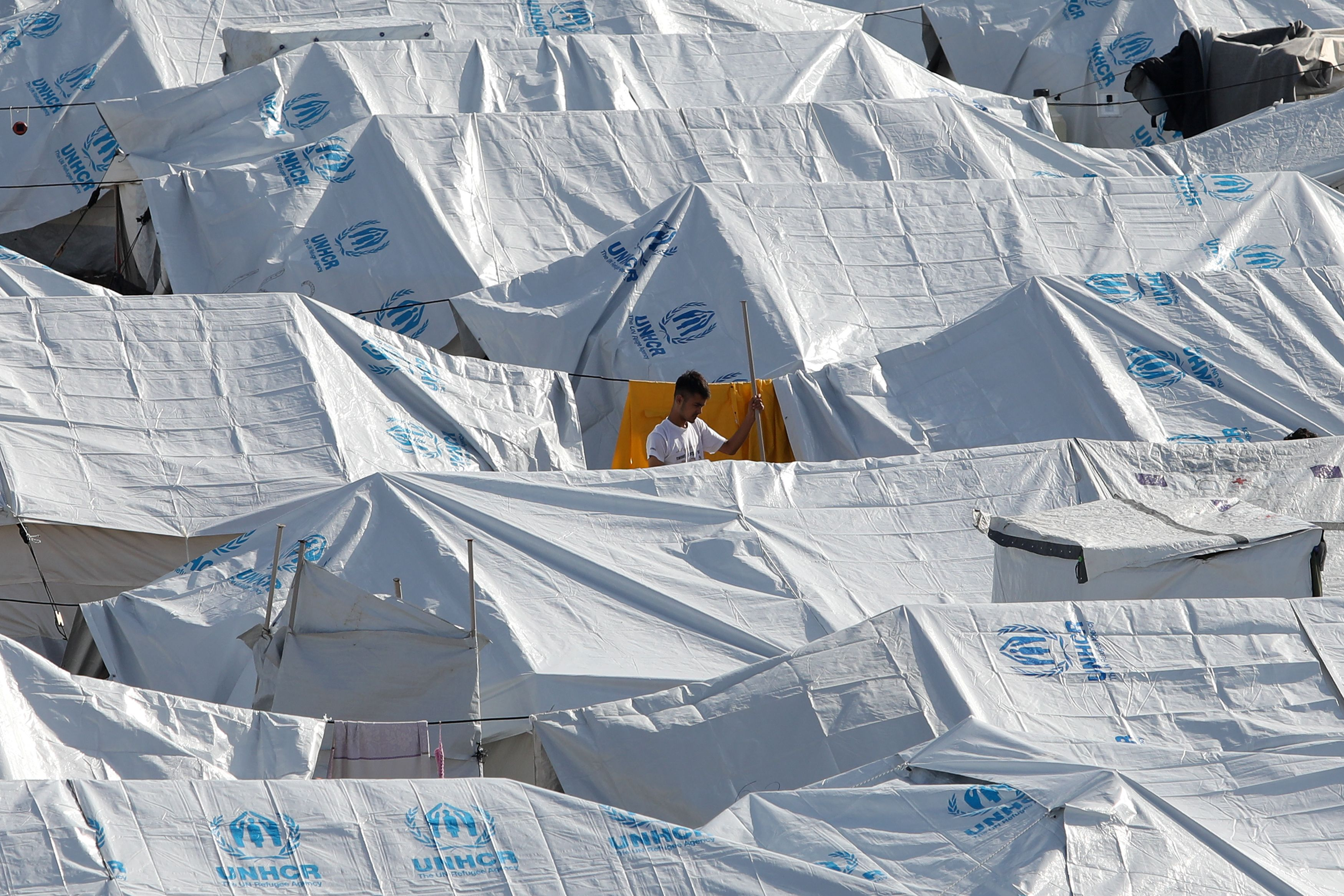 A young man stands among tents in the Kara Tepe camp for refugees and migrants on the island of Lesbos, Greece, October 14, 2020. REUTERS/Elias Marcou