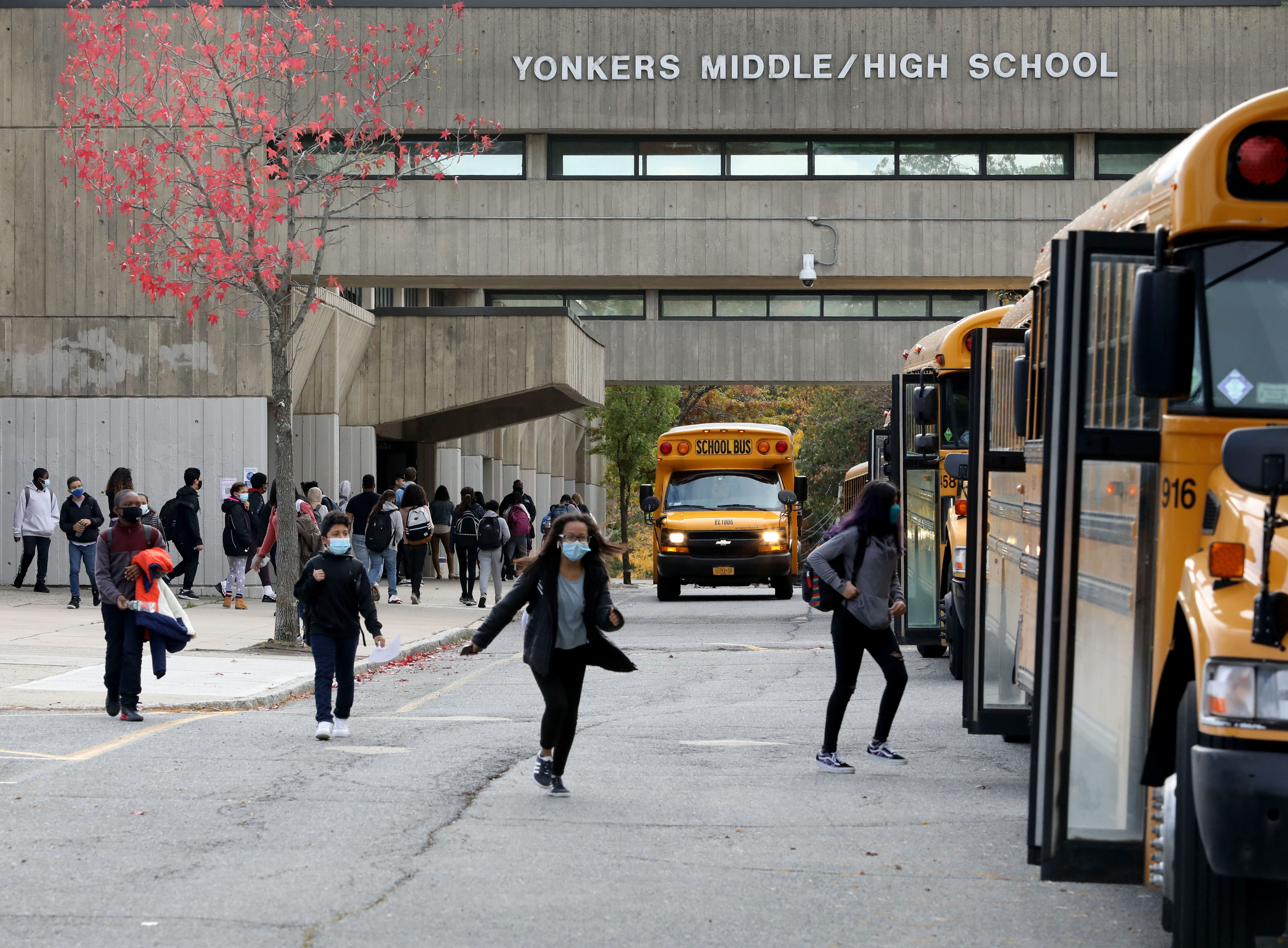Students run toward their school busses after dismissal at Yonkers Middle High School, Oct. 27, 2020.Yonkers School Dismissal