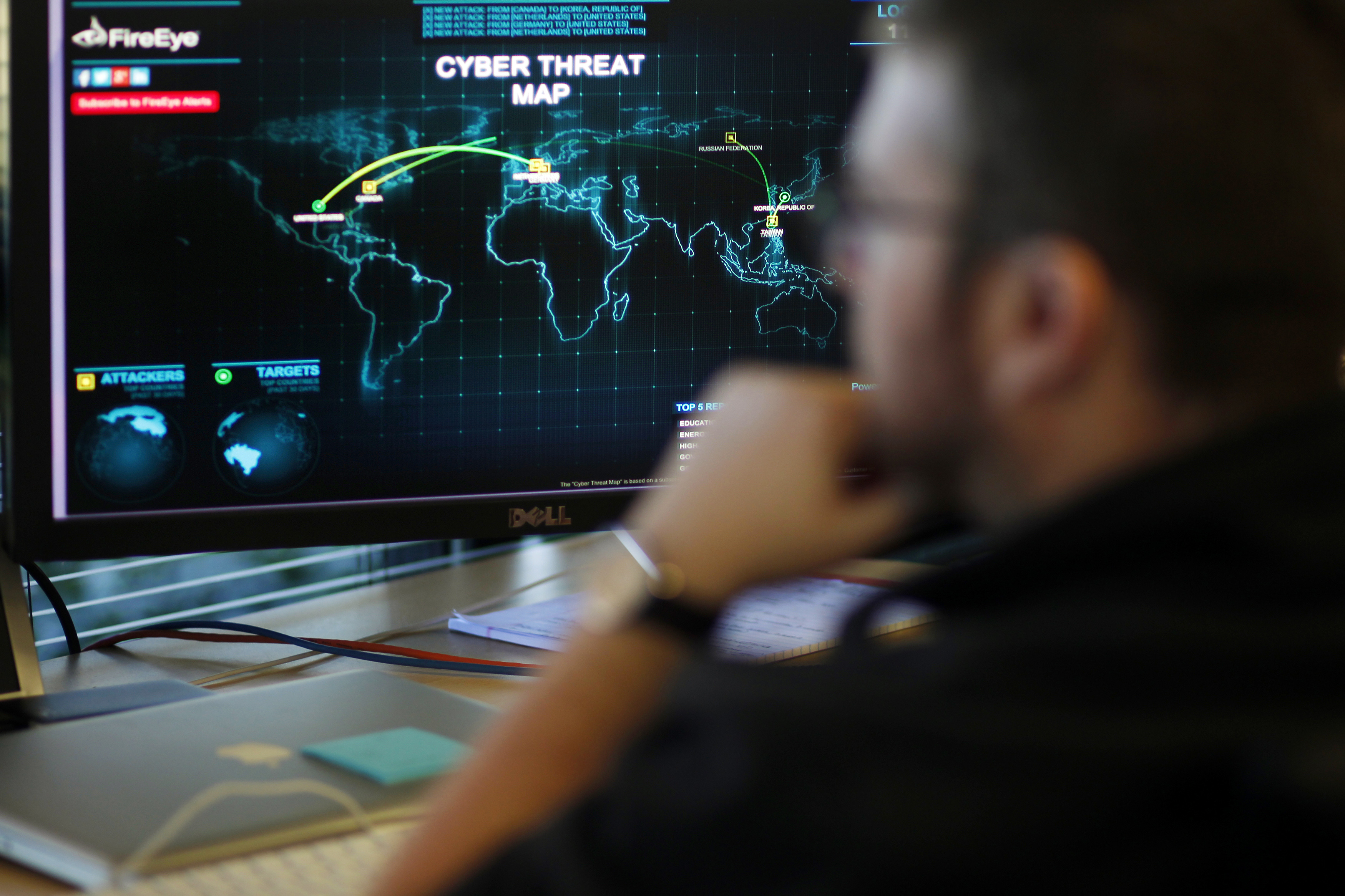 A FireEye information analyst works in front of a screen showing a near real-time map tracking cyber threats at the FireEye office in Milpitas, California, December 29, 2014. FireEye is the security firm hired by Sony to investigate last month's cyberattack against Sony Pictures. Picture taken December 29.     REUTERS/Beck Diefenbach (UNITED STATES - Tags: BUSINESS SCIENCE TECHNOLOGY CRIME LAW)