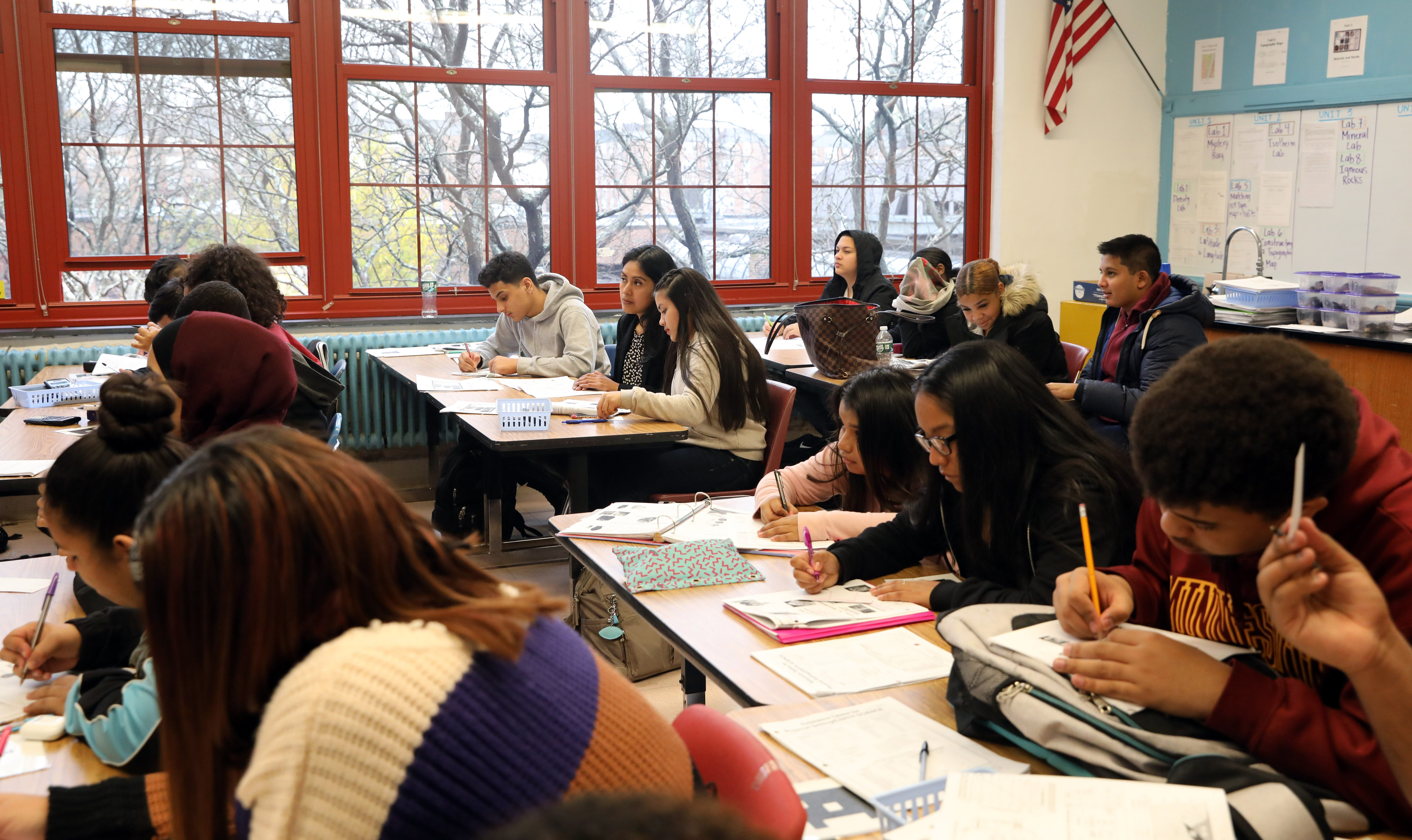 """Catalina Chavez, center, an """"English as a new language"""" teacher works with sophomore Vanessa Mejia, who came to the country two months ago from Guatemala, during Eartth Science class at Roosevelt High School - Early College Studies Nov. 7, 2019 in Yonkers. Fuad Alhomidi, a student from Yemen, works beside them.Secondary"""