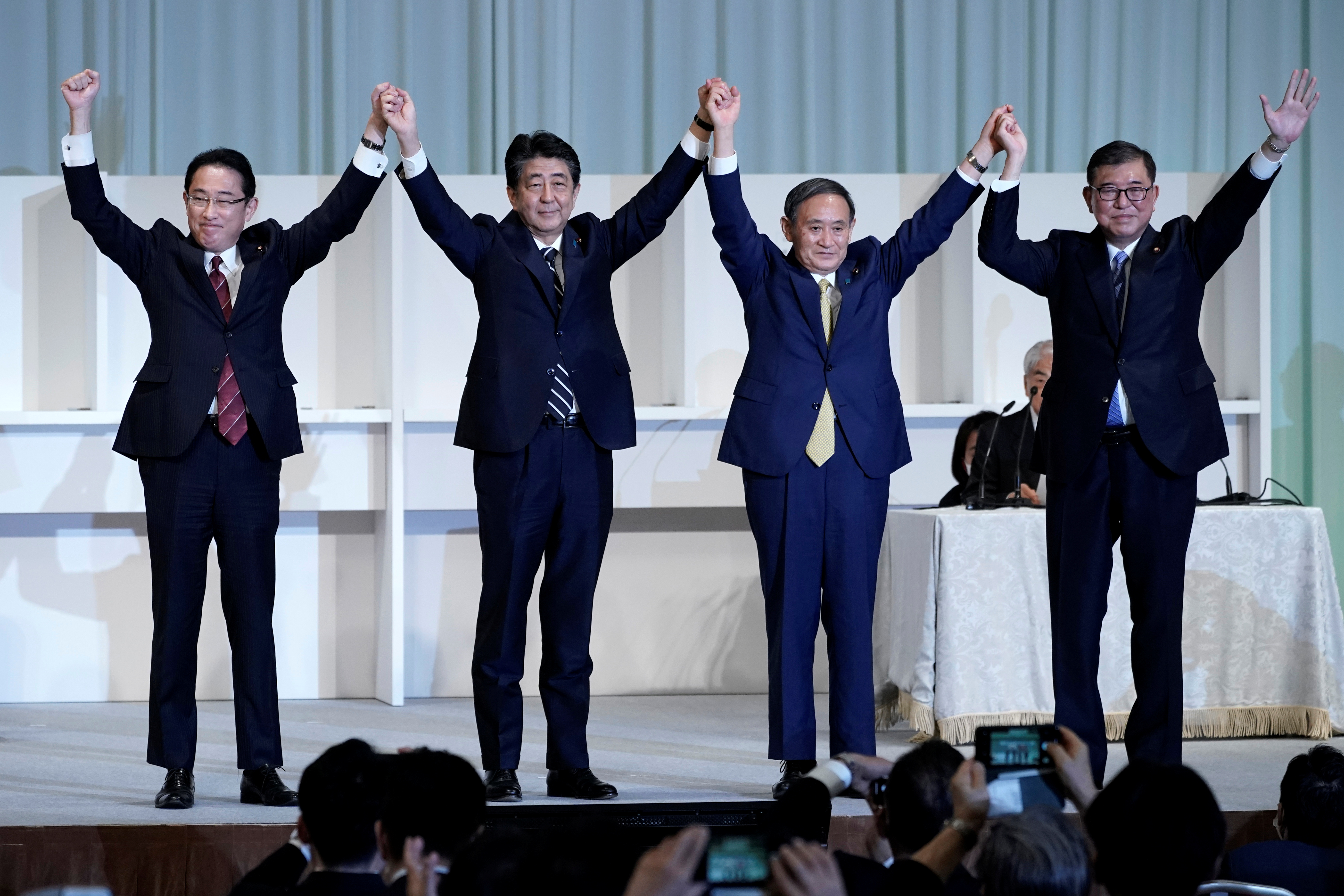 Japan's Prime Minister Shinzo Abe, Chief Cabinet Secretary Yoshihide Suga, former Defense Minister Shigeru Ishiba and former Foreign Minister Fumio Kishida celebrate after Suga was elected as new head of the ruling party at the Liberal Democratic Party's (LDP) leadership election in Tokyo, Japan September 14, 2020. Eugene Hoshiko/Pool via REUTERS