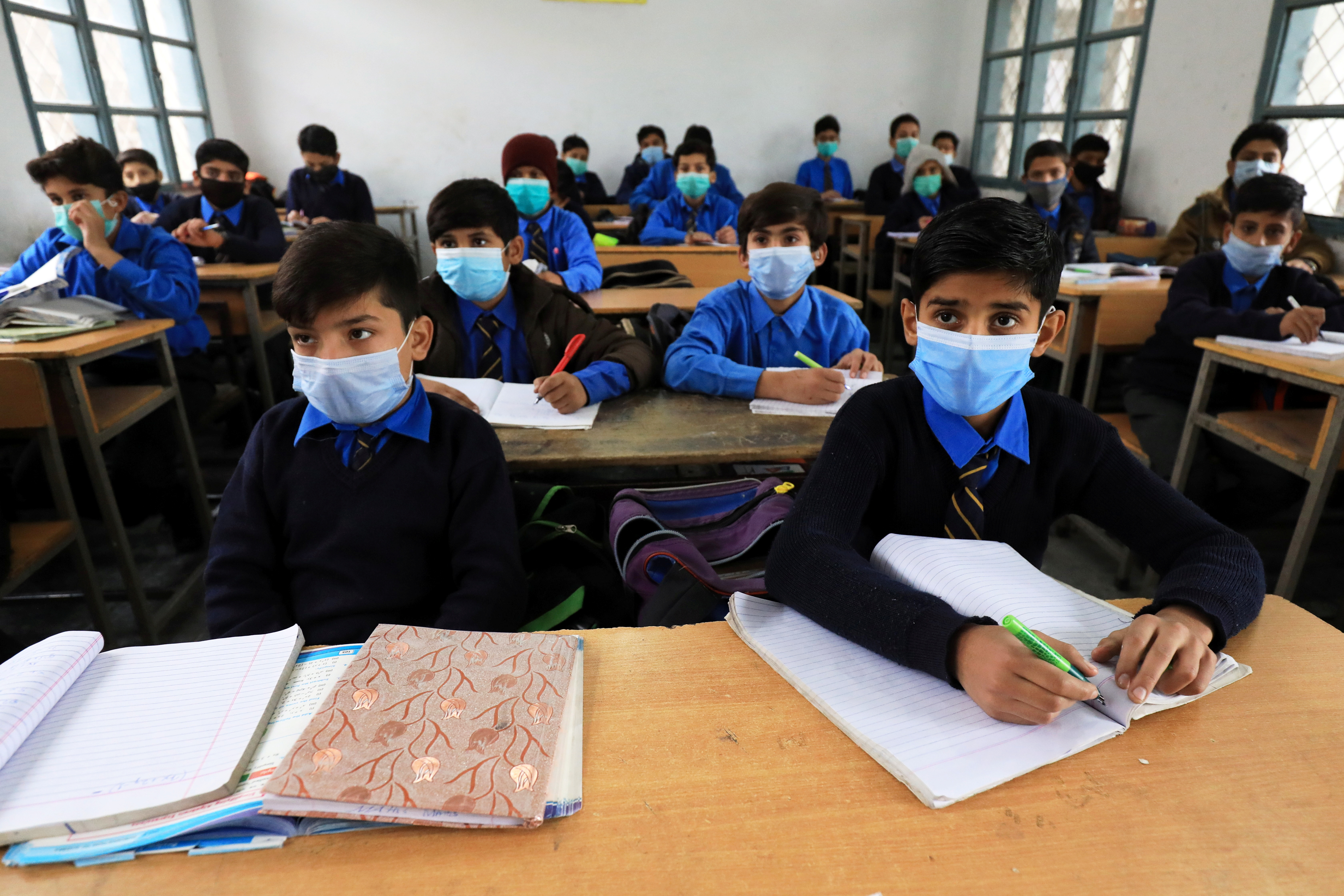 Students wear protective masks as they attend a class at school as the outbreak of the coronavirus disease (COVID-19) continues, in Peshawar, Pakistan November 23, 2020. REUTERS/Fayaz Aziz