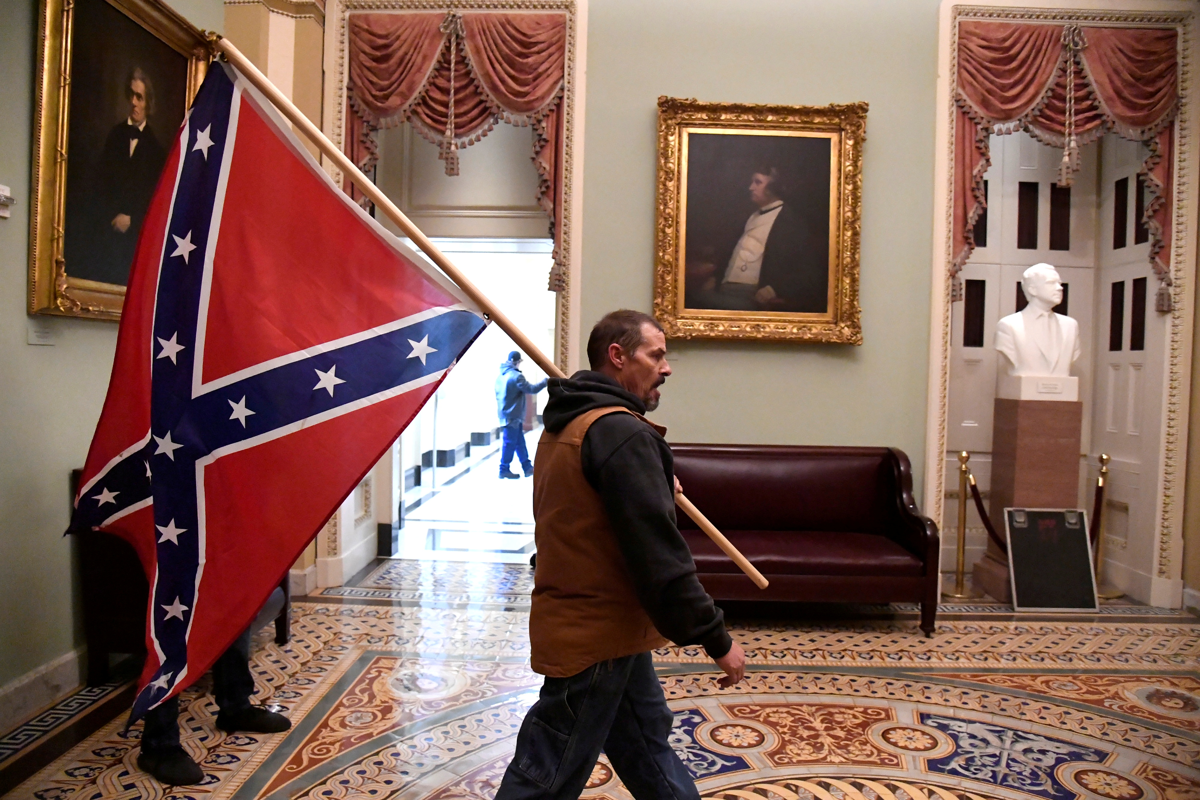 A supporter of President Donald Trump carries a Confederate battle flag on the second floor of the U.S. Capitol near the entrance to the Senate after breaching security defenses, in Washington, U.S., January 6, 2021. A portrait of abolitionist senator Charles Sumner of Massachusetts, who was savagely beaten on the Senate floor after delivering a speech criticizing slavery in 1856, hangs above the couch.        REUTERS/Mike Theiler     TPX IMAGES OF THE DAY