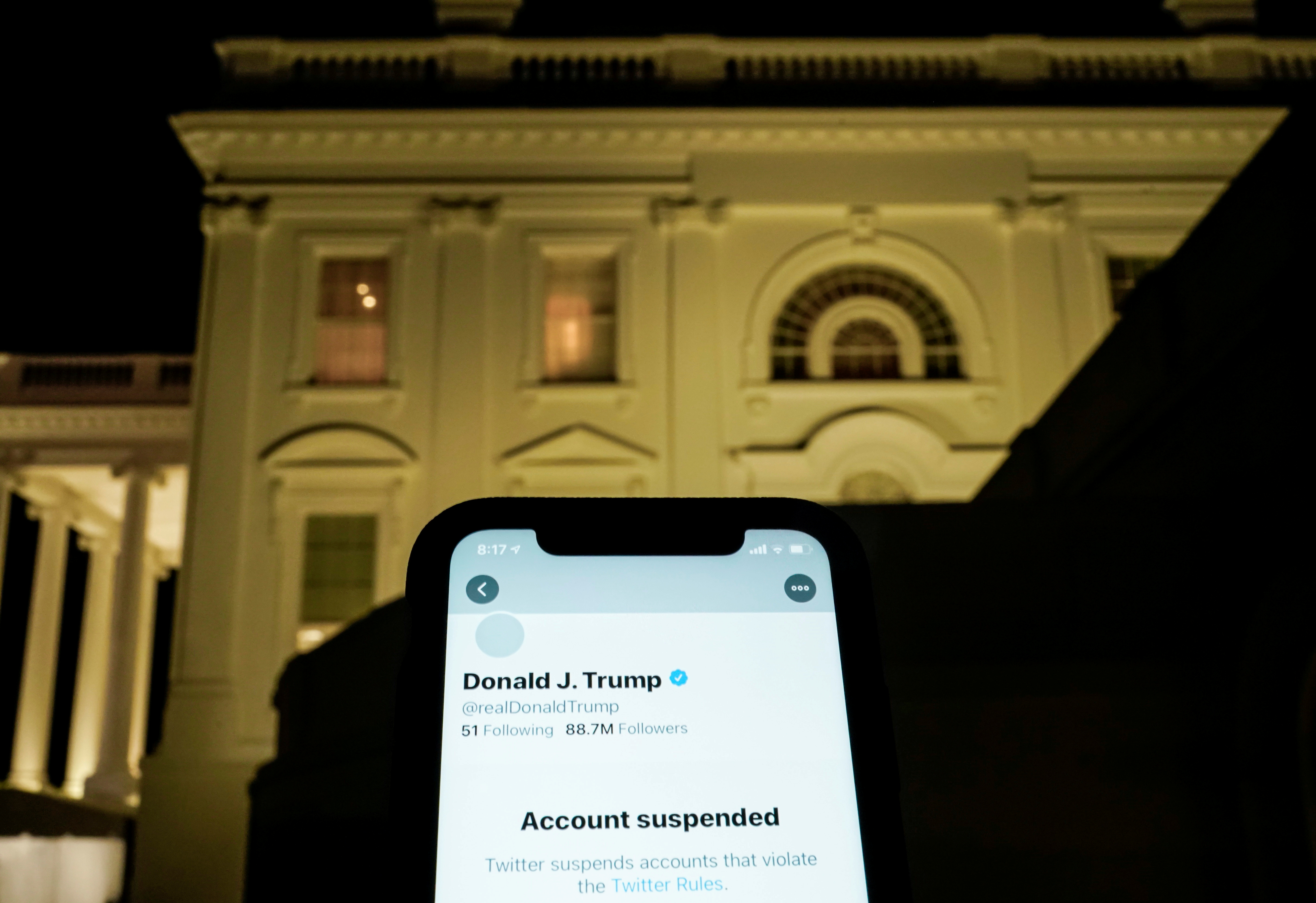 FILE PHOTO: FILE PHOTO: A photo illustration shows the suspended Twitter account of U.S. President Donald Trump on a smartphone and the White House in Washington, U.S., January 8, 2021.  REUTERS/Joshua Roberts/Illustration/File Photo