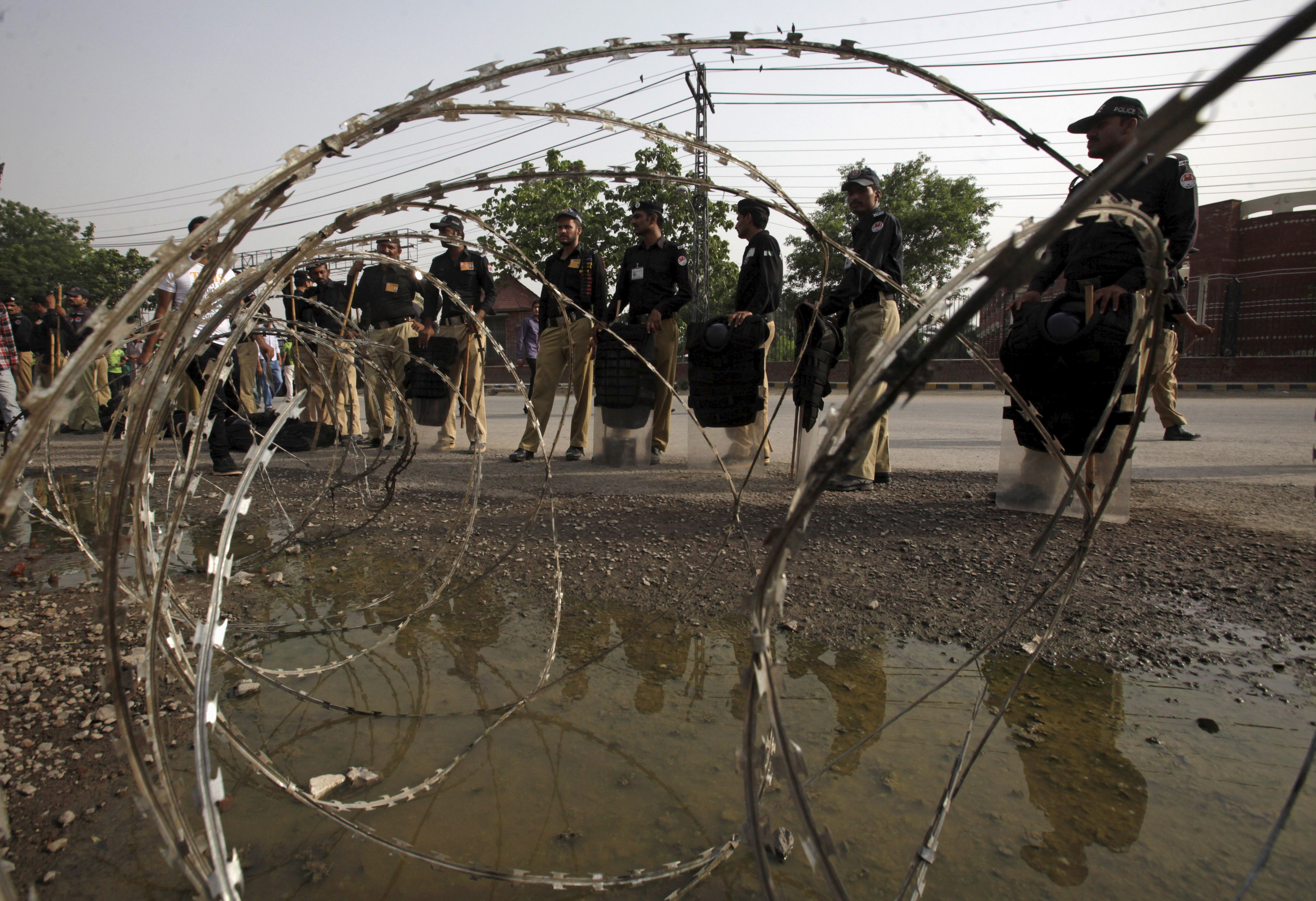 Policemen stand guard beside razor wire outside Gaddafi stadium before the second Twenty20 Cricket match between Pakistan and Zimbabwe in Lahore, Pakistan, May 24, 2015. Zimbabwe is the first test-playing nation to tour Pakistan since a 2009 terror attack on the Sri Lanka team bus in Lahore left the driver dead and several players injured. REUTERS/Mohsin Raza