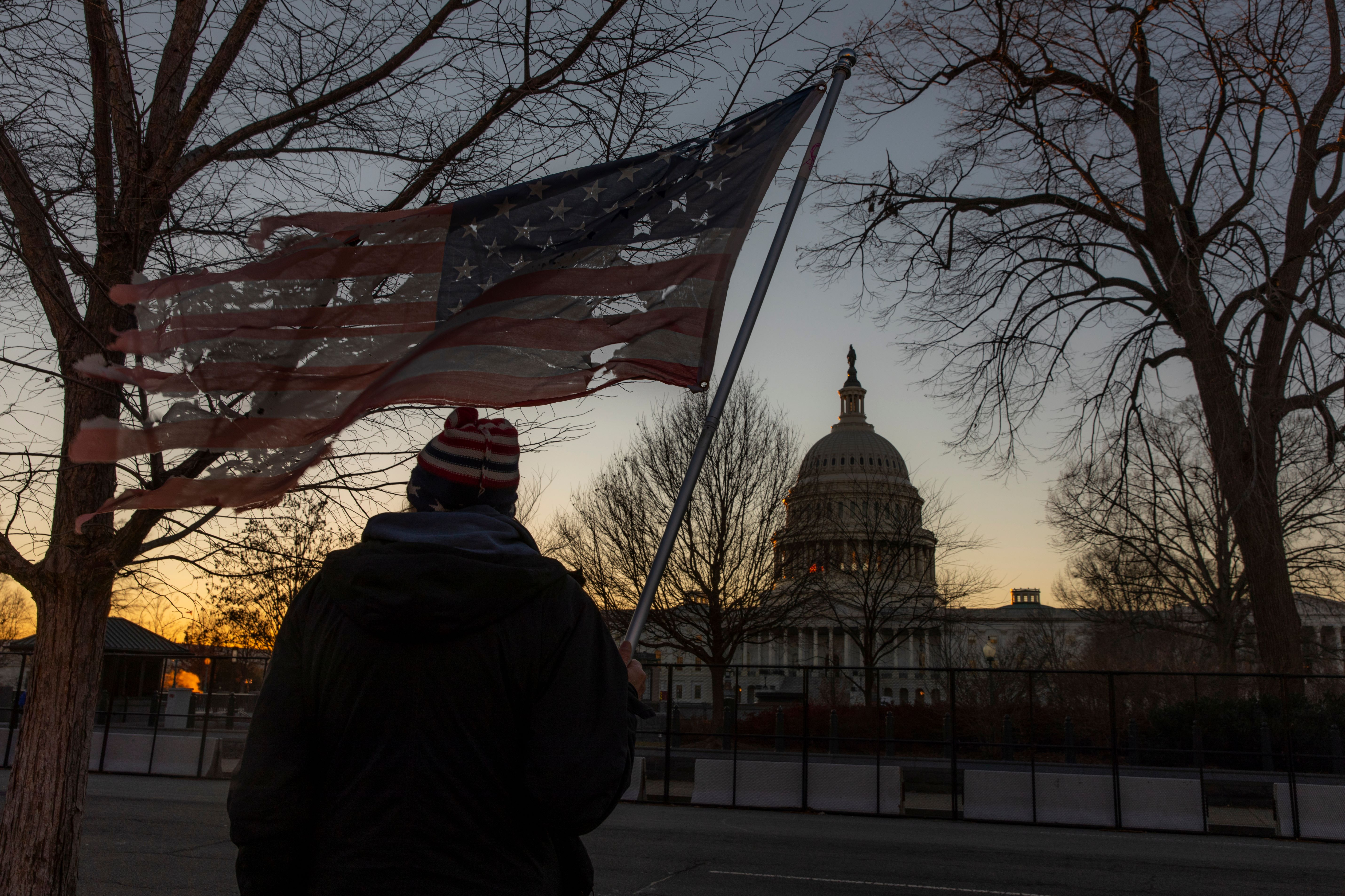 Washington DC, USA - January 9, 2021: A man with a flag watches as additional fencing is installed around the U.S. Capitol after the January 6 riots and ahead of President-Elect Biden's Inauguration.