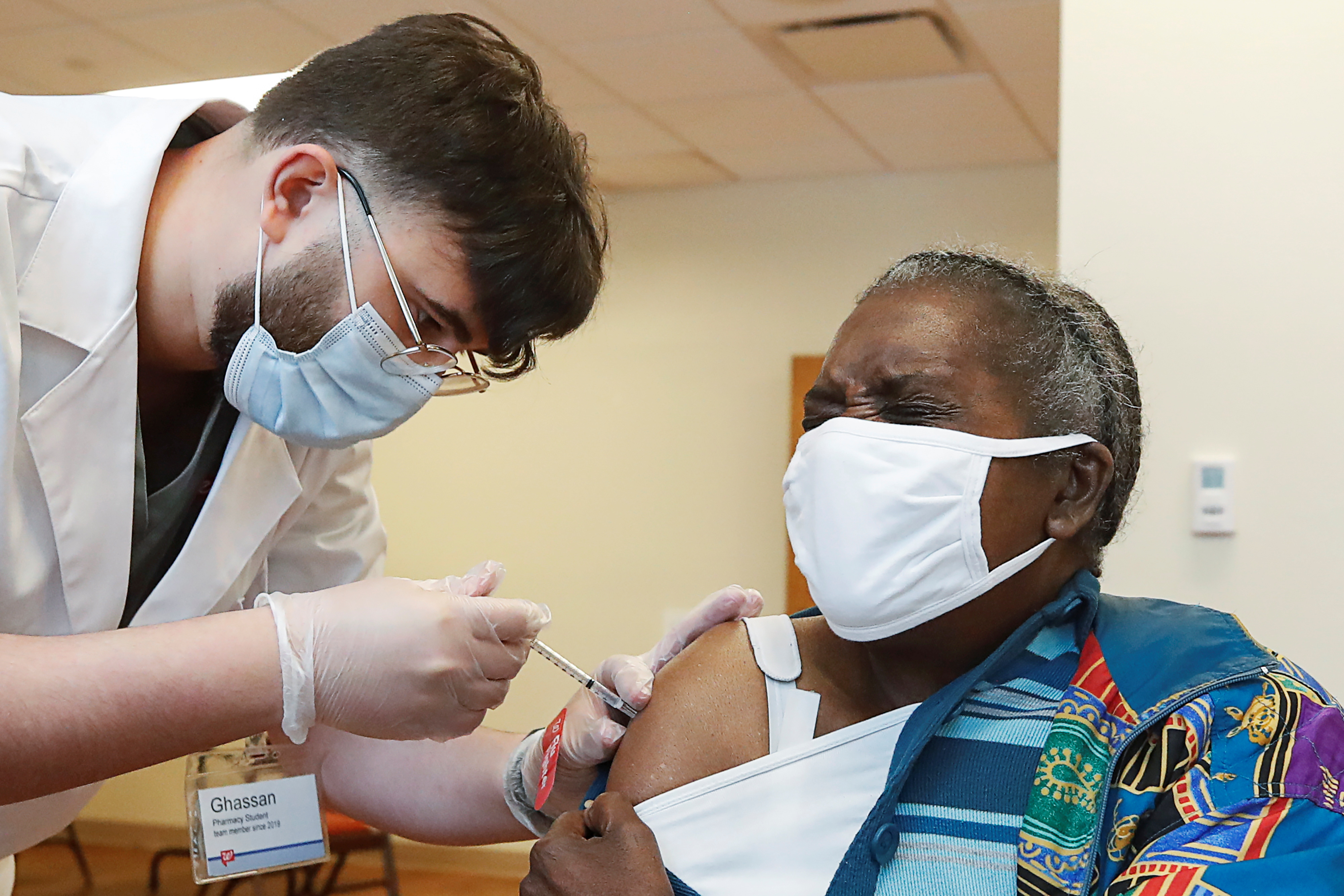 Lillie McCray (R) receives the  Pfizer-BioNTech vaccine against coronavirus disease (COVID-19) from Walgreens healthcare professional Ghassan Ayyad (L) at the Victor Walchirk Apartments in Evanston, Illinois, U.S. February 22, 2021.  REUTERS/Kamil Krzaczynski