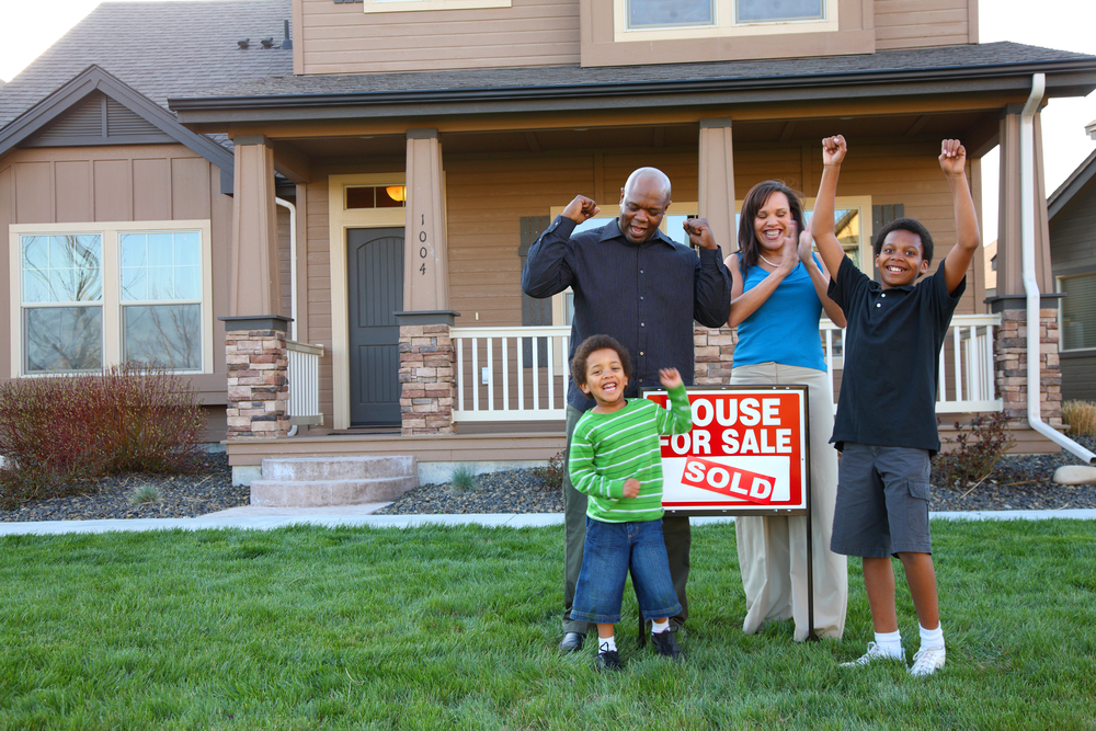 Family celebrating in front of house with for-sale sign