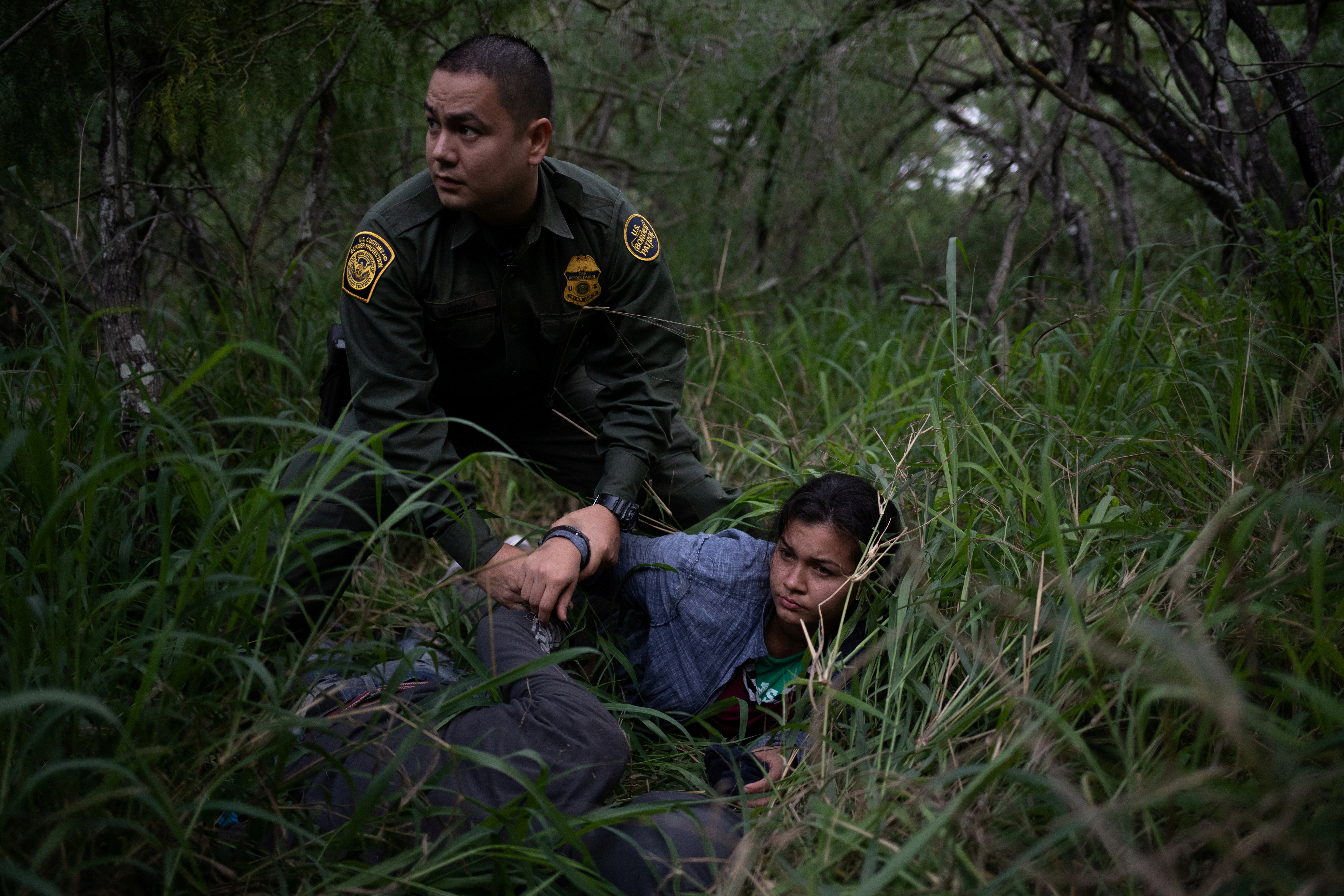 """A border patrol agent apprehends a woman and a man after they were caught illegally crossing into the U.S. border from Mexico near McAllen, Texas, U.S., May 2, 2018. Reuters photographer Adrees Latif: """"One could hardly tell there were people lying in the brush even as a U.S. Border Patrol agent stood over these migrants. They were tracked into the brush by their shoe prints. The group of nine had taken cover overnight and were apprehended the following morning for illegally crossing into the U.S. from Mexico."""" REUTERS/Adrees Latif  SEARCH """"IMMIGRATION POY"""" FOR THIS STORY. SEARCH """"REUTERS POY"""" FOR ALL BEST OF 2018 PACKAGES. TPX IMAGES OF THE DAY."""
