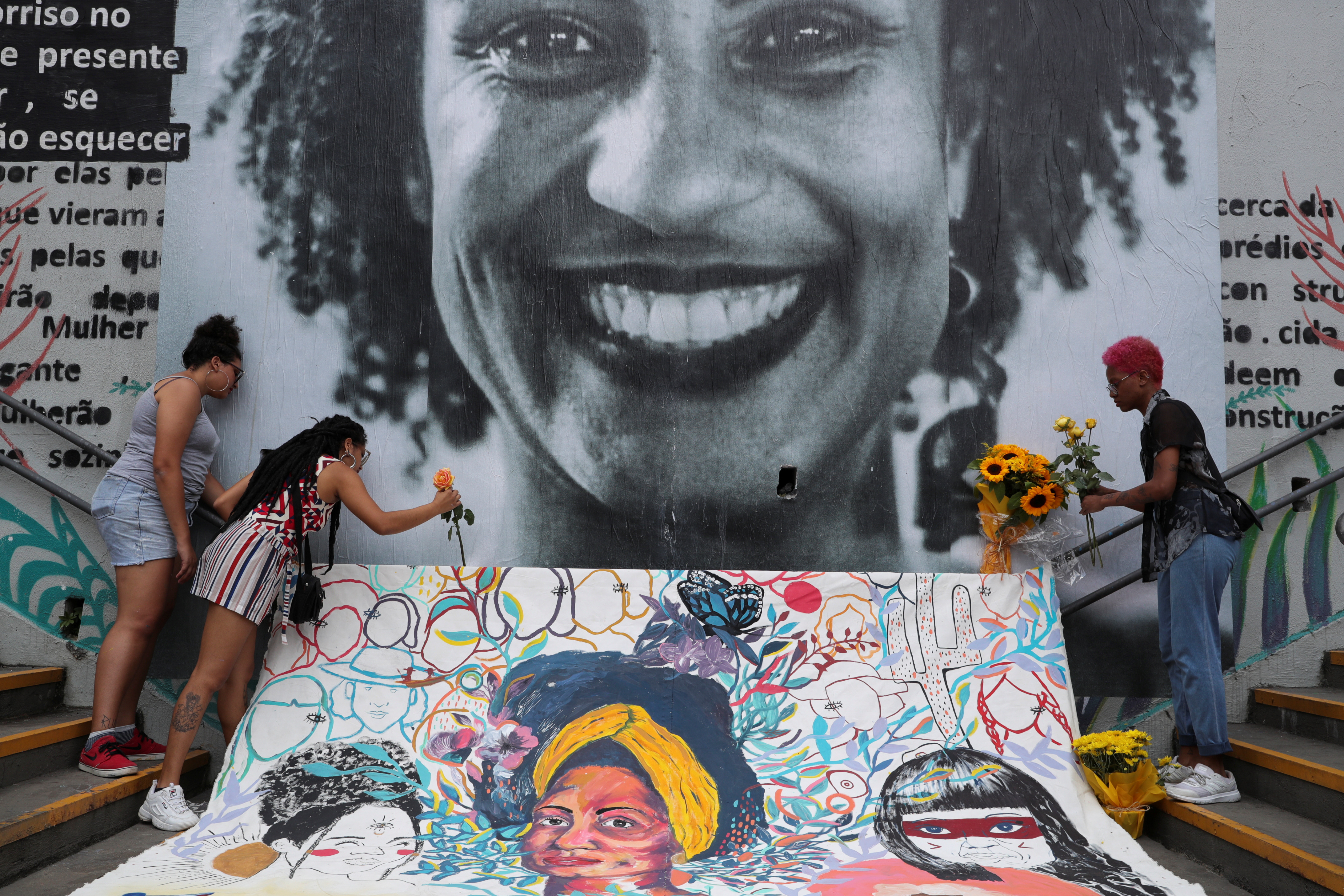 Women lay flowers at a mural of the murdered Brazilian human rights activist Marielle Franco.